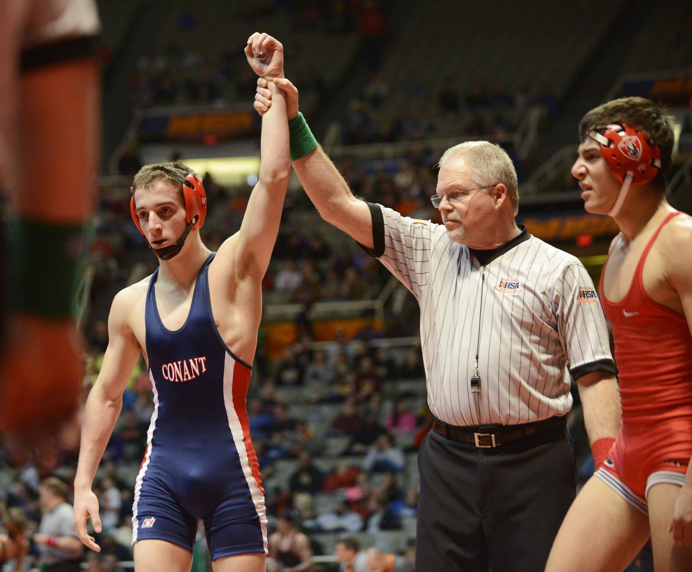 Bobby Alexander of Conant High School is declared the winner after beating Ameen Hamdan of Marist High School Saturday in the 132-pound weight class third place match of the wrestling IHSA Class 3A state tournament at State Farm Center in Champaign.