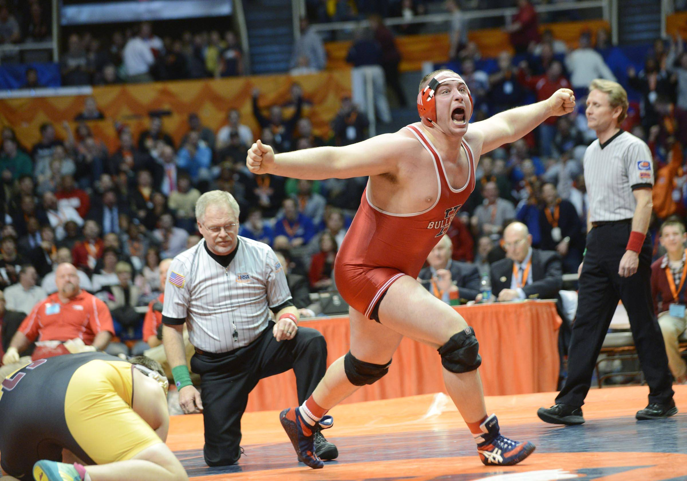 Tanner Farmer of Highland High School celebrates his win against Michael Johnshon of Lombard Montini Catholic High School Saturday in the 285-pound weight class championship match of the wrestling IHSA Class 2A state tournament at State Farm Center in Champaign.