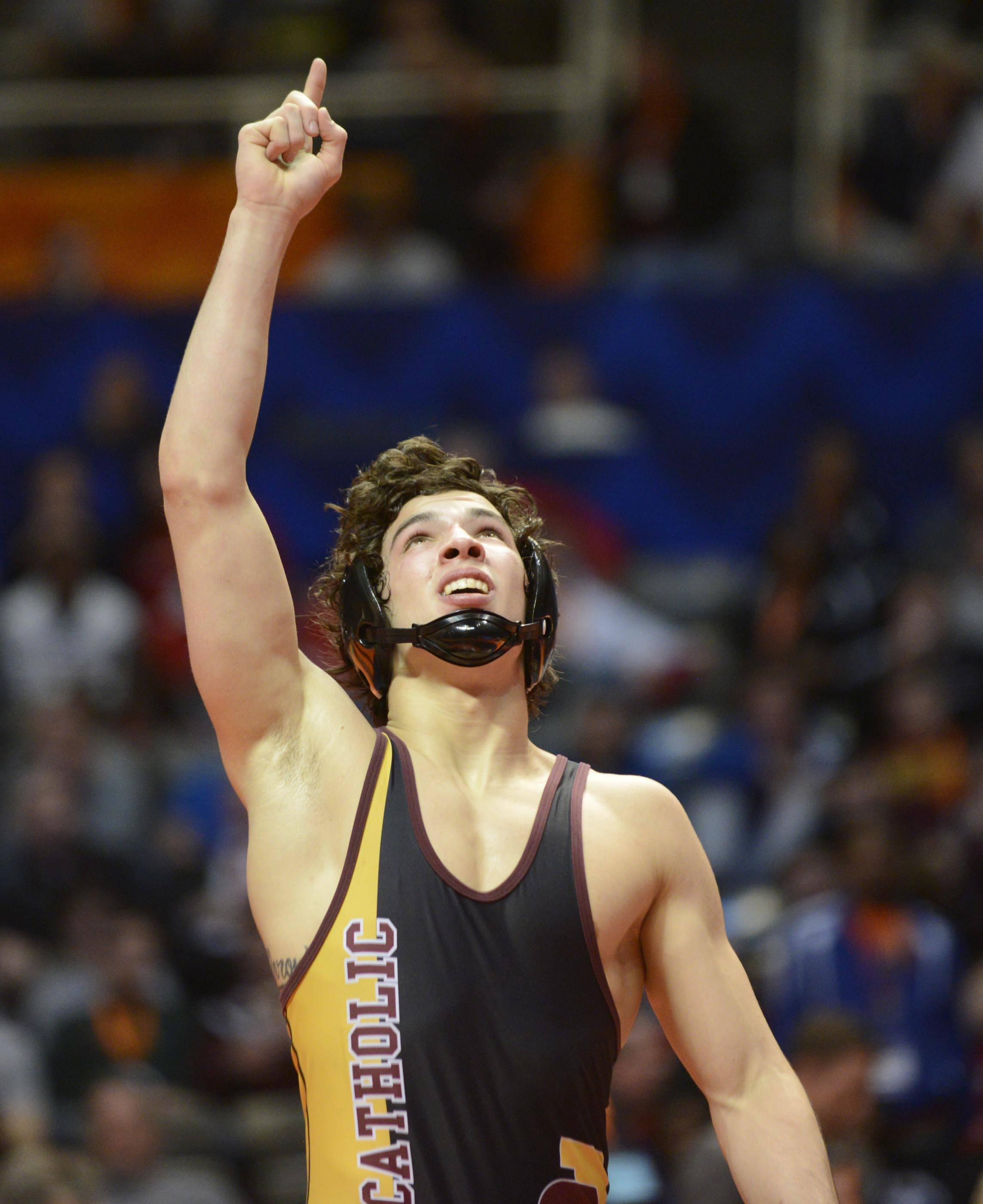 Vincent Turk of Lombard Montini Catholic High School points up after winning against Randle Taborn of Springfield High School Saturday in the 138-pound weight class championship match of the wrestling IHSA Class 2A state tournament at State Farm Center in Champaign.