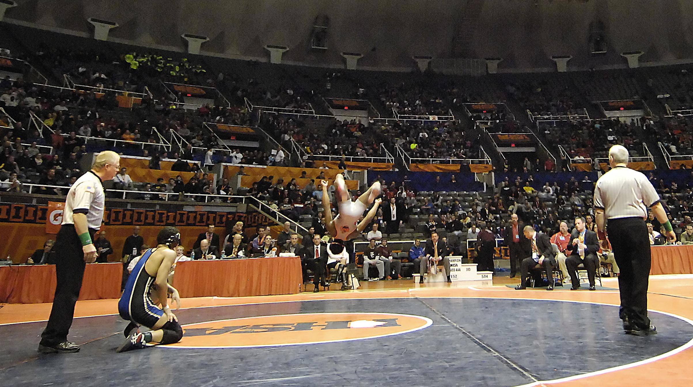 Emery Parker of Gurnee Warren Township High School watches as Kamal Bey of Oak Park River Forest High School does a back flip after winning Saturday in the 160-pound weight class championship match of the wrestling IHSA Class 3A state tournament at State Farm Center in Champaign.