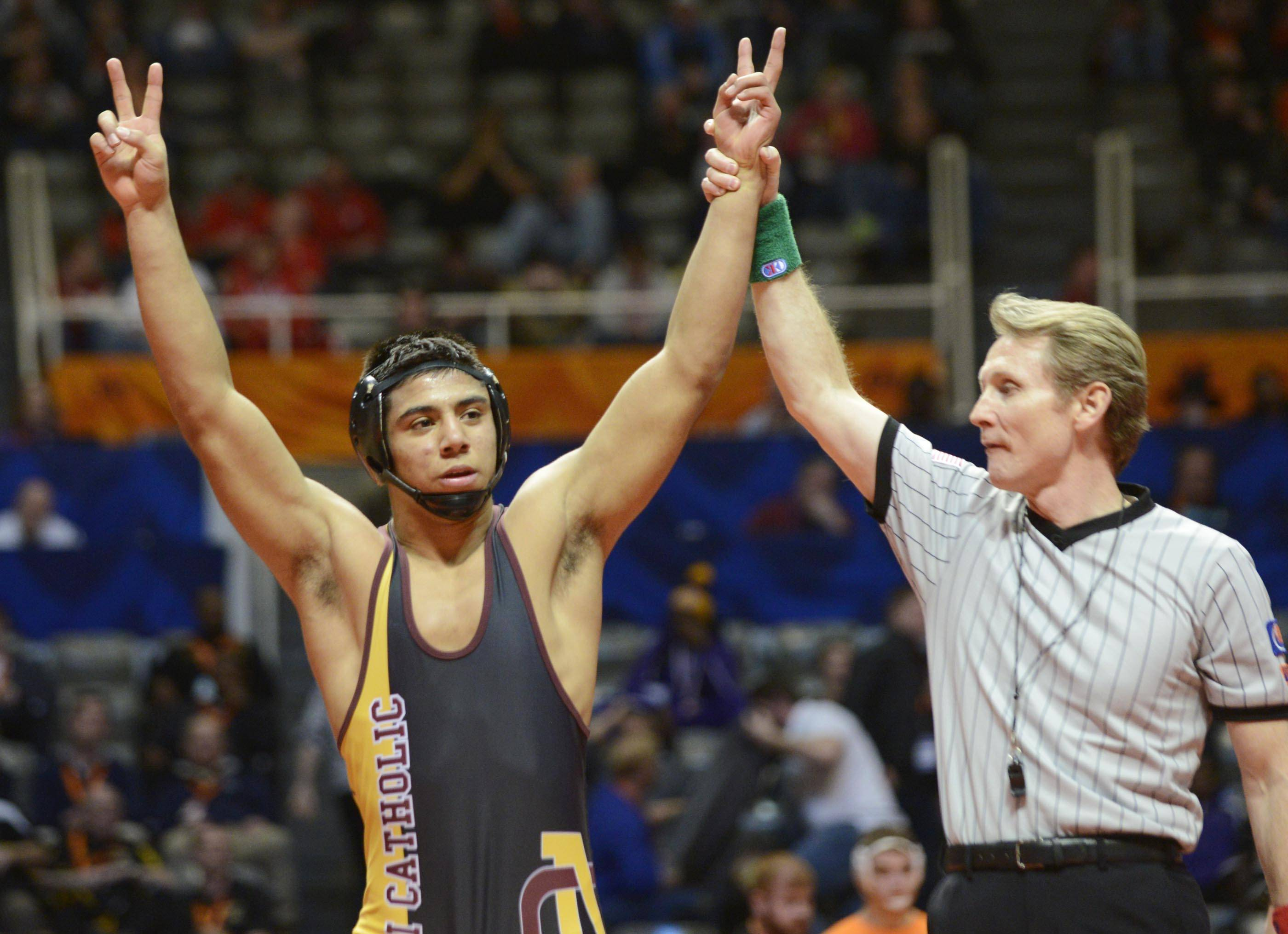 Xavier Montalvo of Lombard Montini Catholic High School is declared the winner against Eric Schultz of Tinley Park High School Saturday in the 170-pound weight class championship match of the wrestling IHSA Class 2A state tournament at State Farm Center in Champaign.