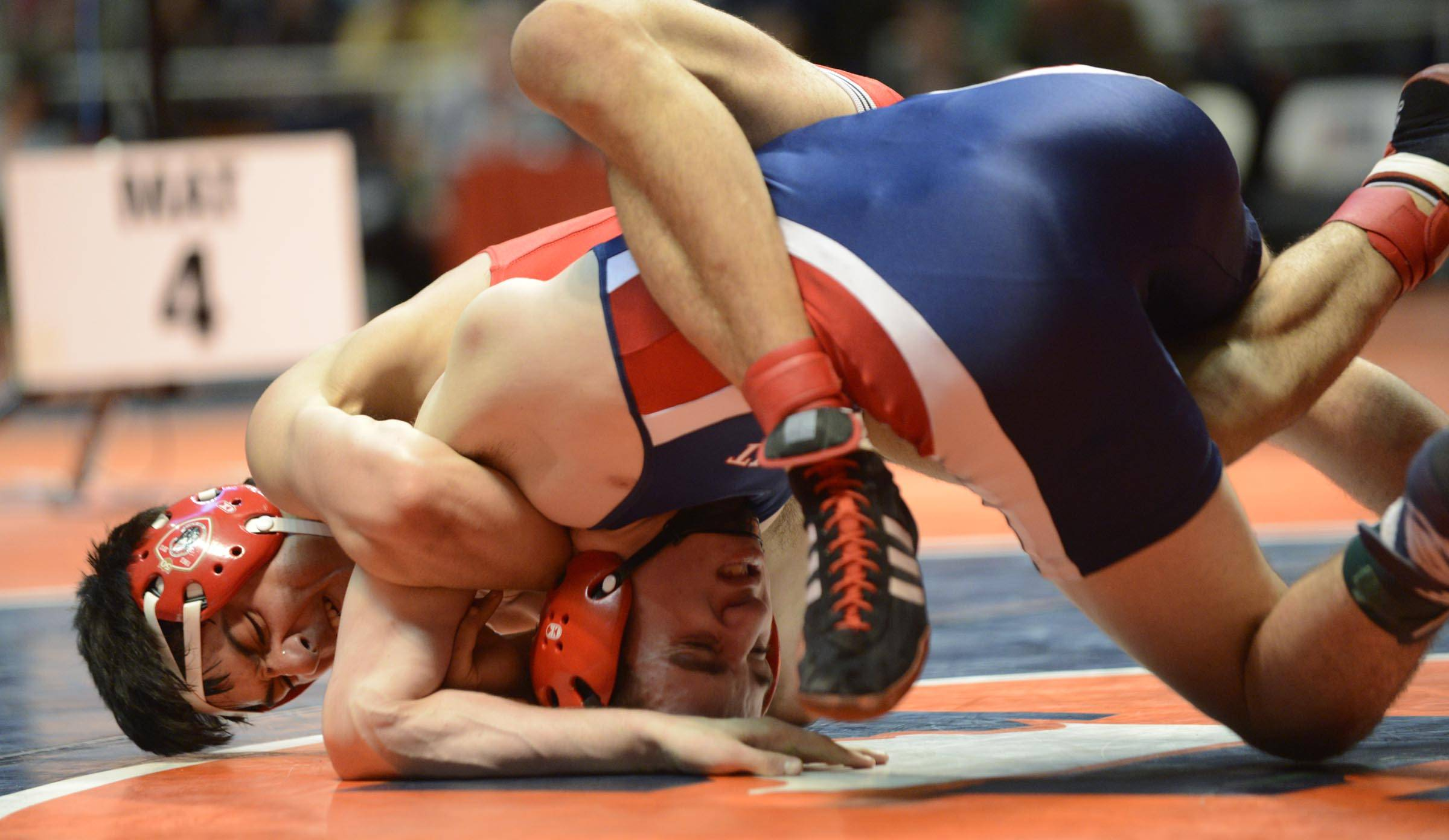 Bobby Alexander of Conant High School, bottom, competes against Ameen Hamdan of Marist High School Saturday in the 132-pound weight class third place match of the wrestling IHSA Class 3A state tournament at State Farm Center in Champaign.