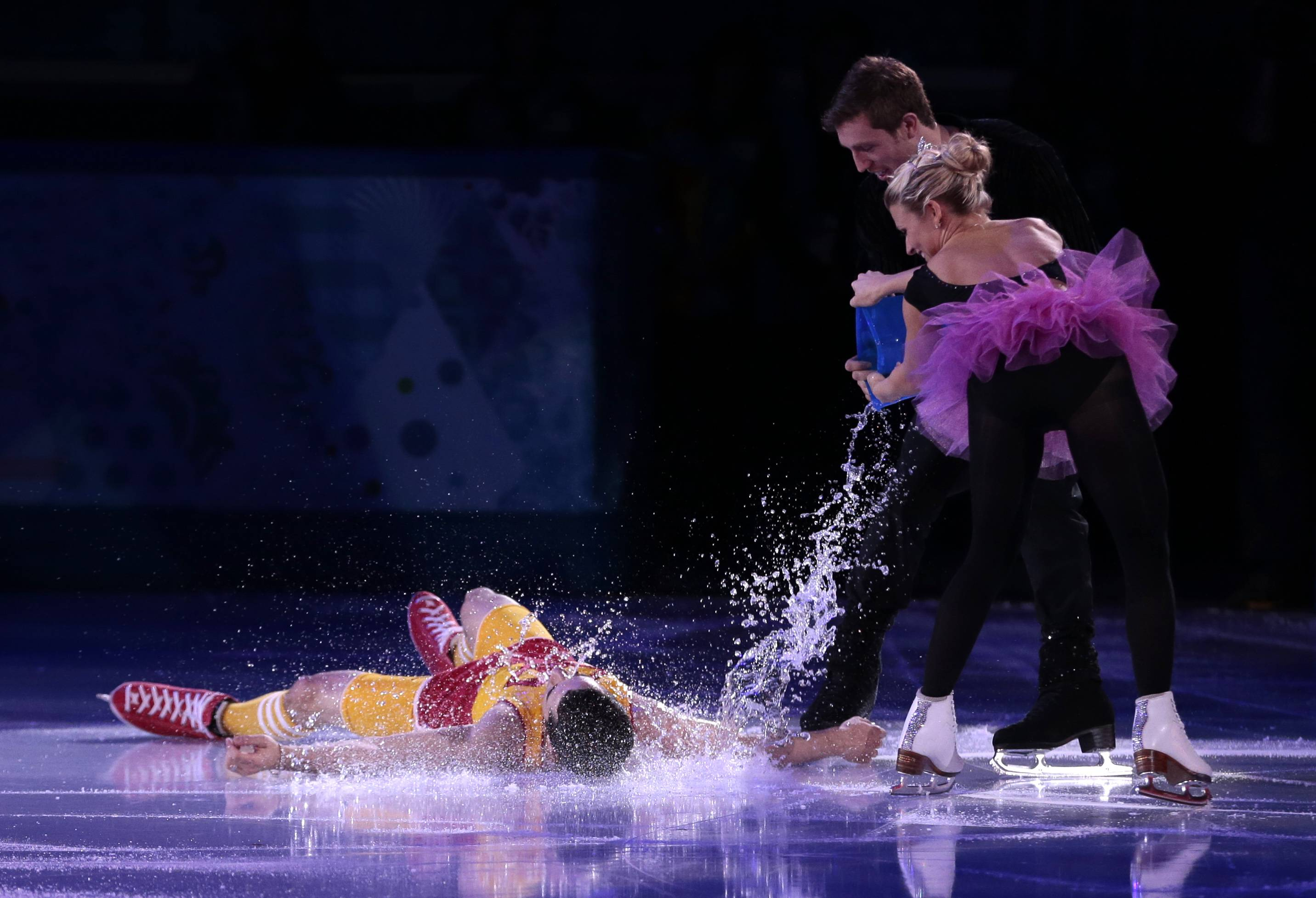 Javier Fernandez of Spain, left, has water poured over him by Kirsten Moore-Towers and Dylan Moscovitch of Canada as they perform during the figure skating exhibition gala at the Iceberg Skating Palace during the 2014 Winter Olympics, Saturday, Feb. 22, 2014, in Sochi, Russia.