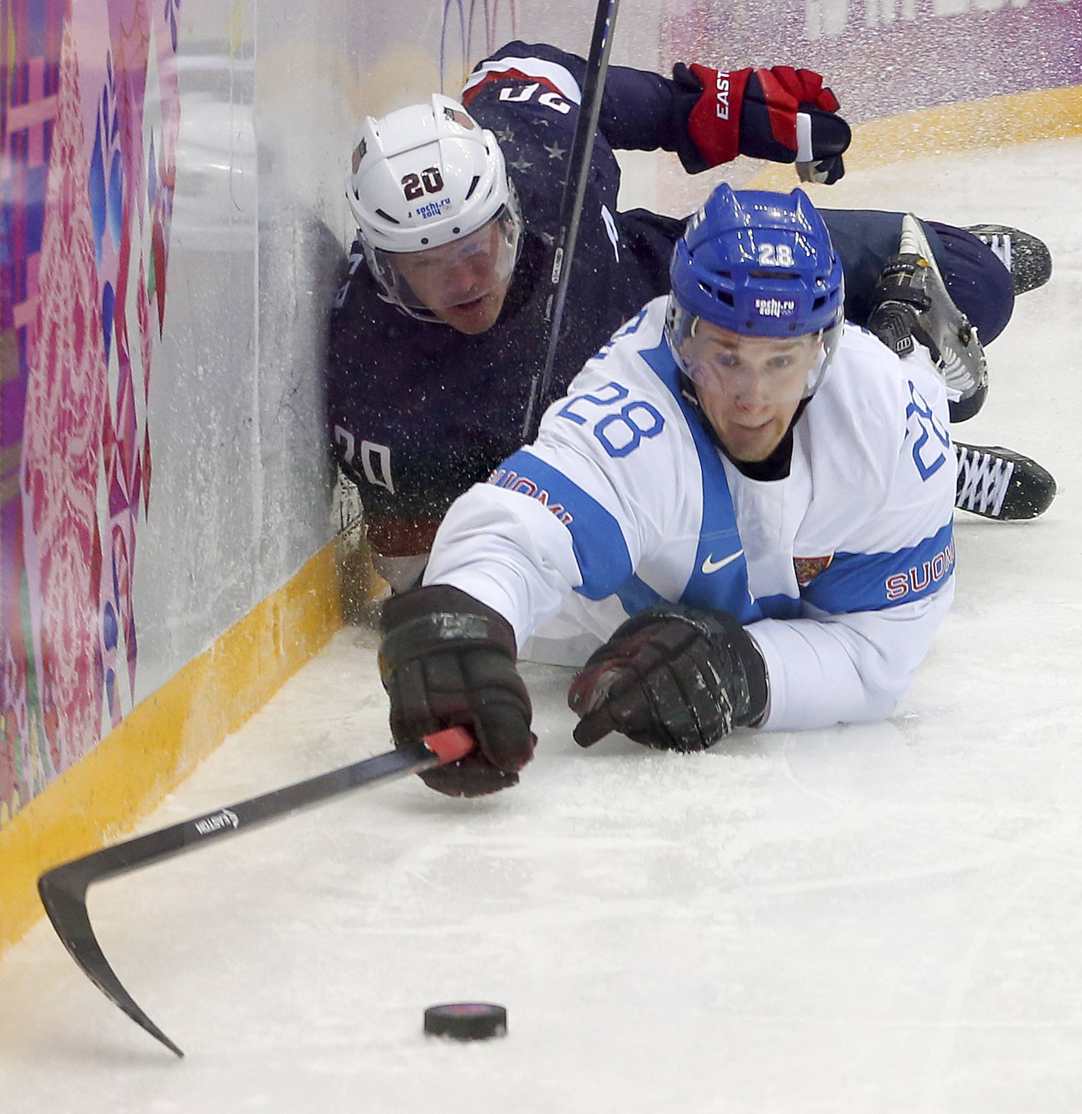 USA forward Blake Wheeler and USA defenseman dive for the puck during the third period of the men's bronze medal ice hockey game at the 2014 Winter Olympics, Saturday, Feb. 22, 2014, in Sochi, Russia.
