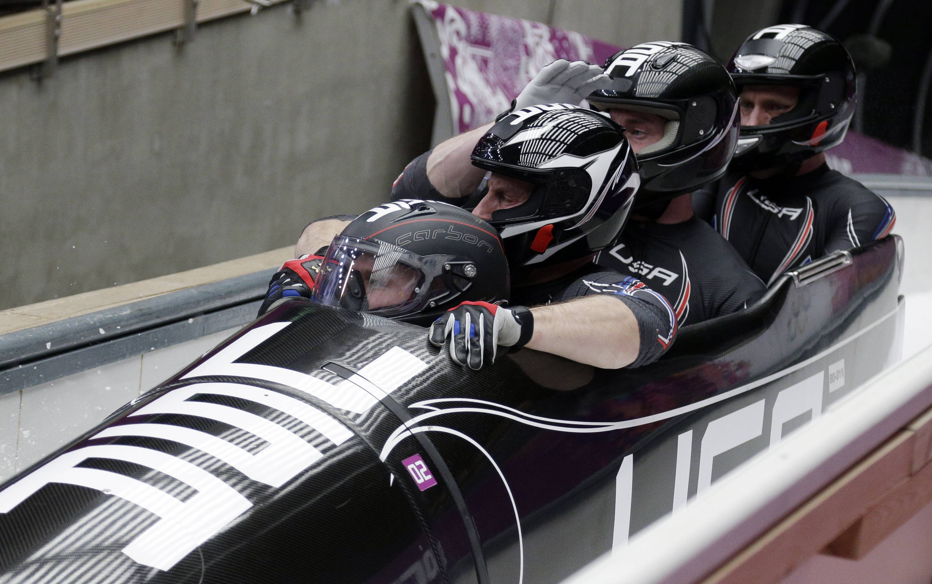 The team from the United States USA-1, with Steven Holcomb, Curtis Tomasevicz, Steven Langton and Christopher Fogt, brake in the finish area after their second run during the men's four-man bobsled competition at the 2014 Winter Olympics, Saturday, Feb. 22, 2014, in Krasnaya Polyana, Russia.