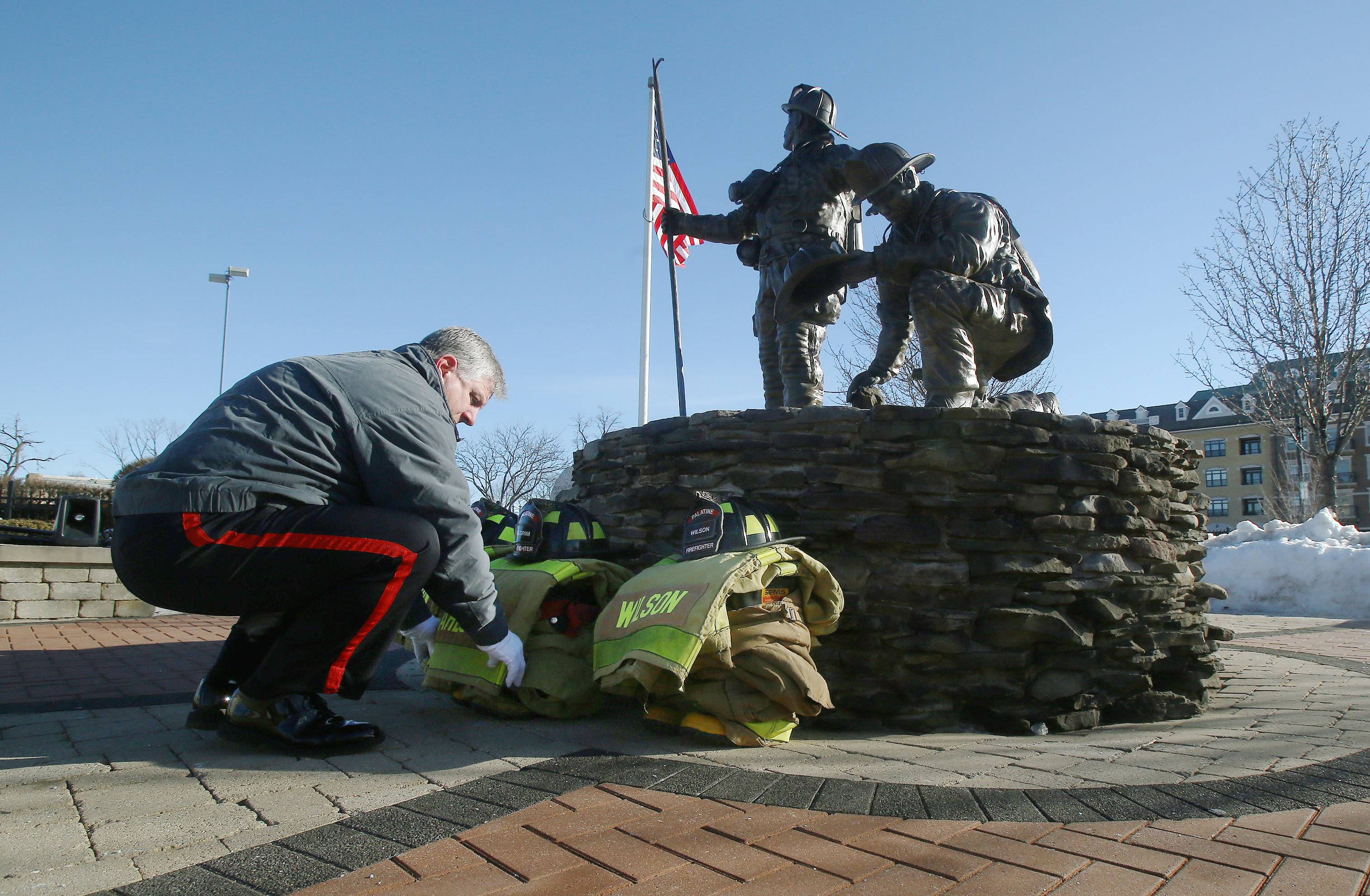 Palatine firefighter Kevin Piasecki adjusts the equipment set in front of the Palatine Firefighters Memorial downtown Sunday before the annual ceremony honoring three volunteer firefighters who died in the line of duty Feb. 23, 1973. Firefighters John Wilson, Richard Freeman and Warren Ahlgrim lost their lives fighting a fire in the Ben Franklin store in the village's downtown.