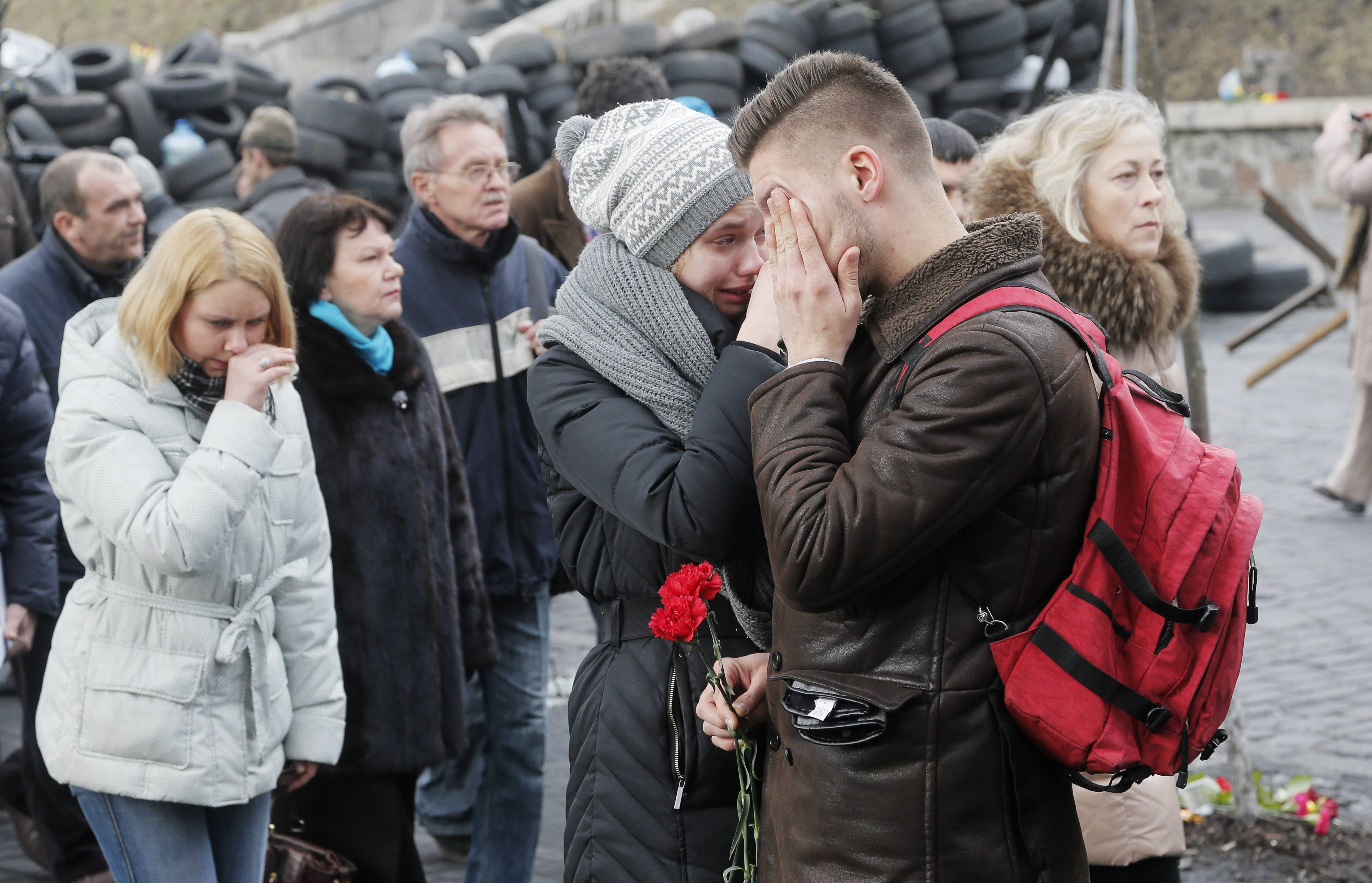 People cry as they pass by the site of recent deadly clashes between opposition protesters and riot police close to Kiev's Independence Square, Ukraine, Sunday. Official reports say 82 people were killed in the recent unrest.