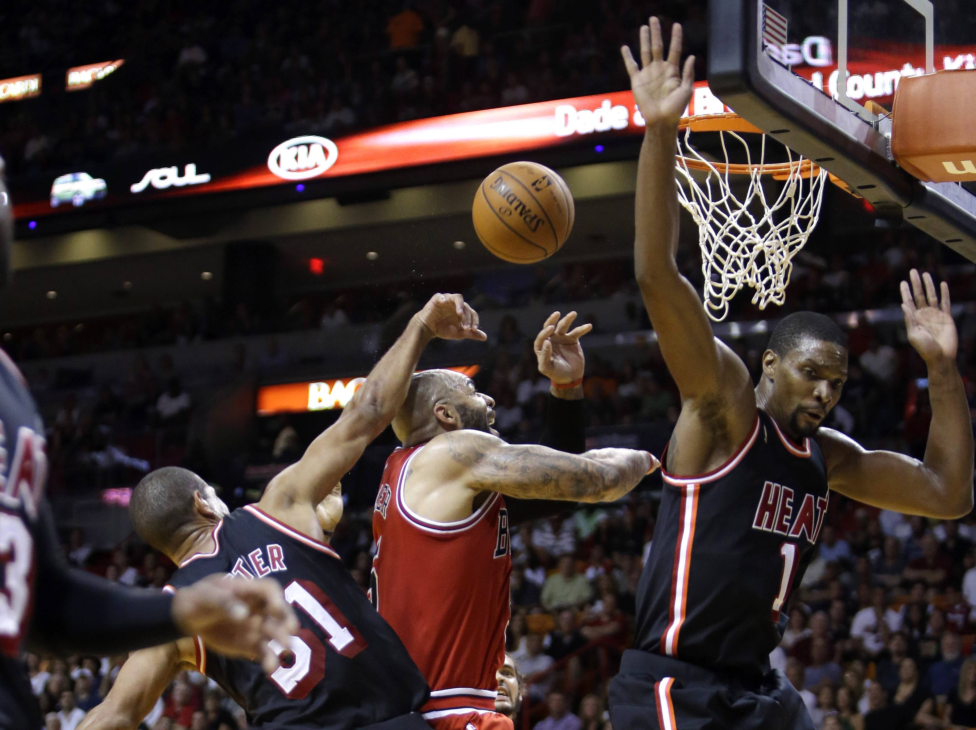 Chicago Bulls' Carlos Boozer, center, is fouled by Miami Heat's Shane Battier (31) during the second half of an NBA basketball game, Sunday, Feb. 23, 2014, in Miami. The Heat defeated the Bulls 93-79. At right is Heat's Chris Bosh (1).