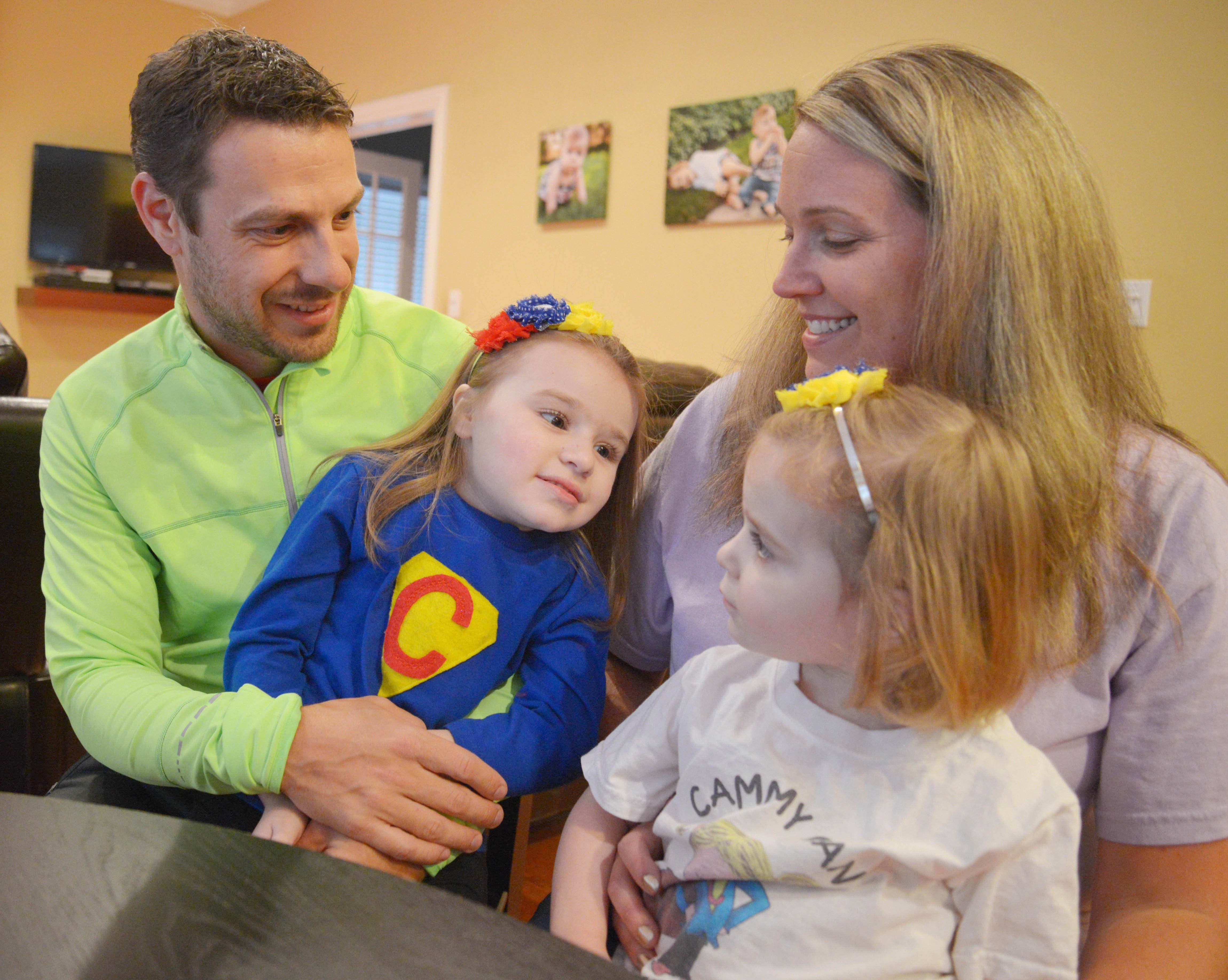 Wearing her Cammy Can superhero outfit, Cameron and her younger sister, Ryan, enjoy some quality lap time with parents Bill and Jackie Babiarz in their Wheaton home.