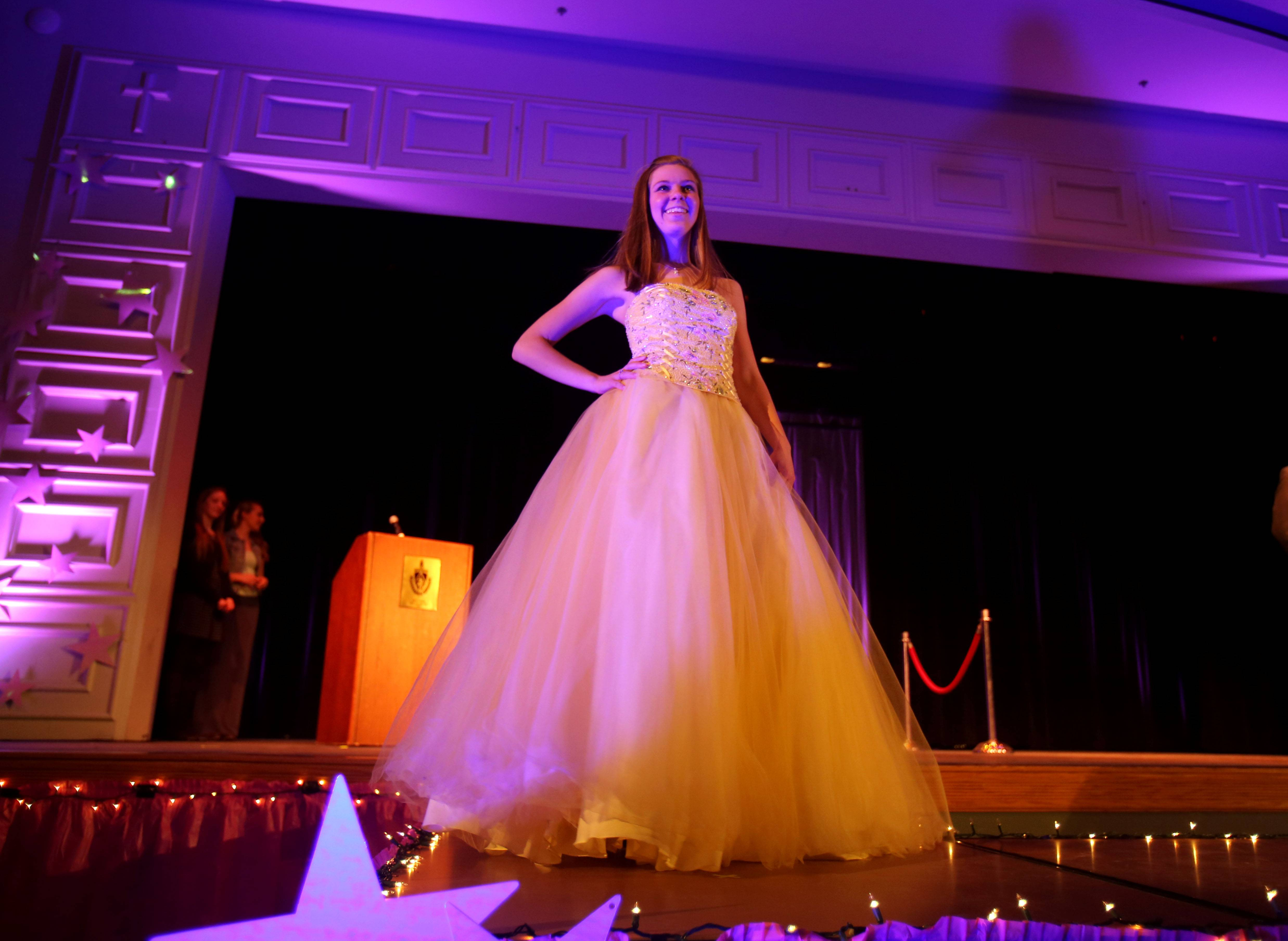 Rosary High School senior Emily Schneider models a prom dress Sunday during the 4th annual Rosary National Honor Society dress sale and fashion show in Aurora. The event raises money for scholarships given to incoming freshmen.