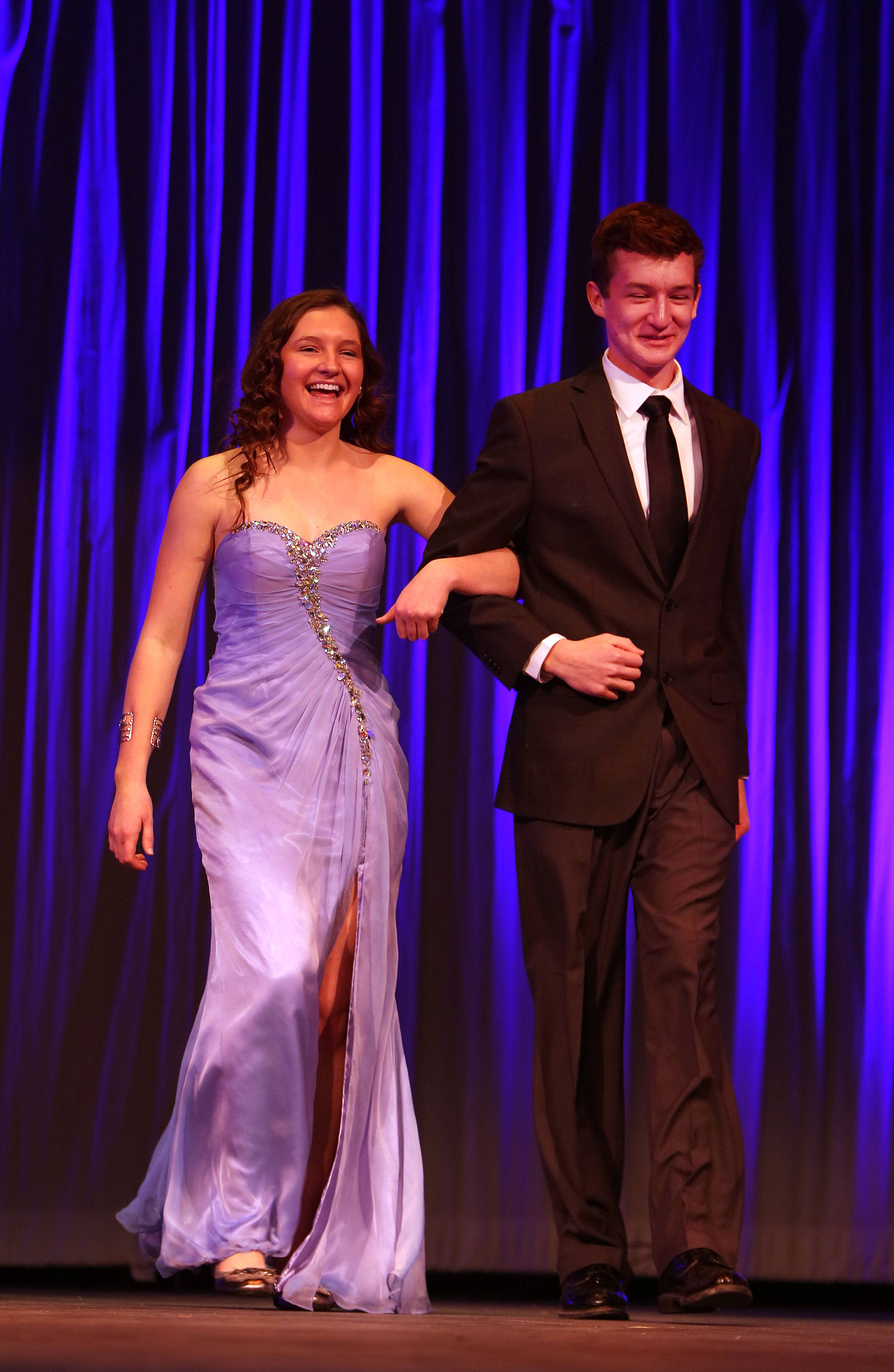 Rosary High School senior Monica Powers, left, is escorted by her brother, Marmion Academy sophomore Jimmy Powers, during Sunday's 4th annual Rosary National Honor Society dress sale and fashion show in Aurora. The event raises money for scholarships given to incoming freshmen.
