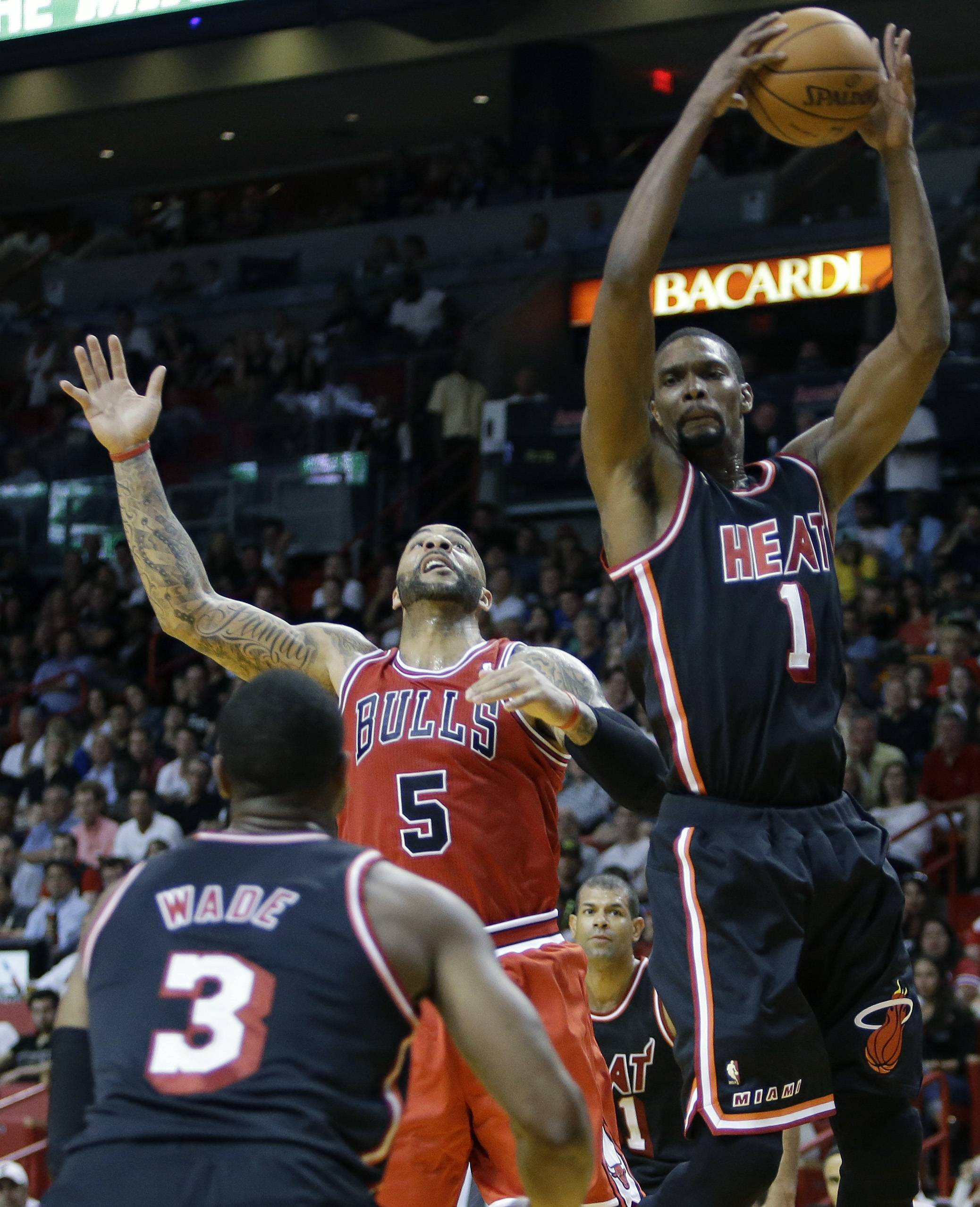 The Heat's Chris Bosh grabs a rebound over the Bulls' Carlos Boozer during the second half Sunday, when Miami went on a 16-2 run at the end of the third quarter to pull away.