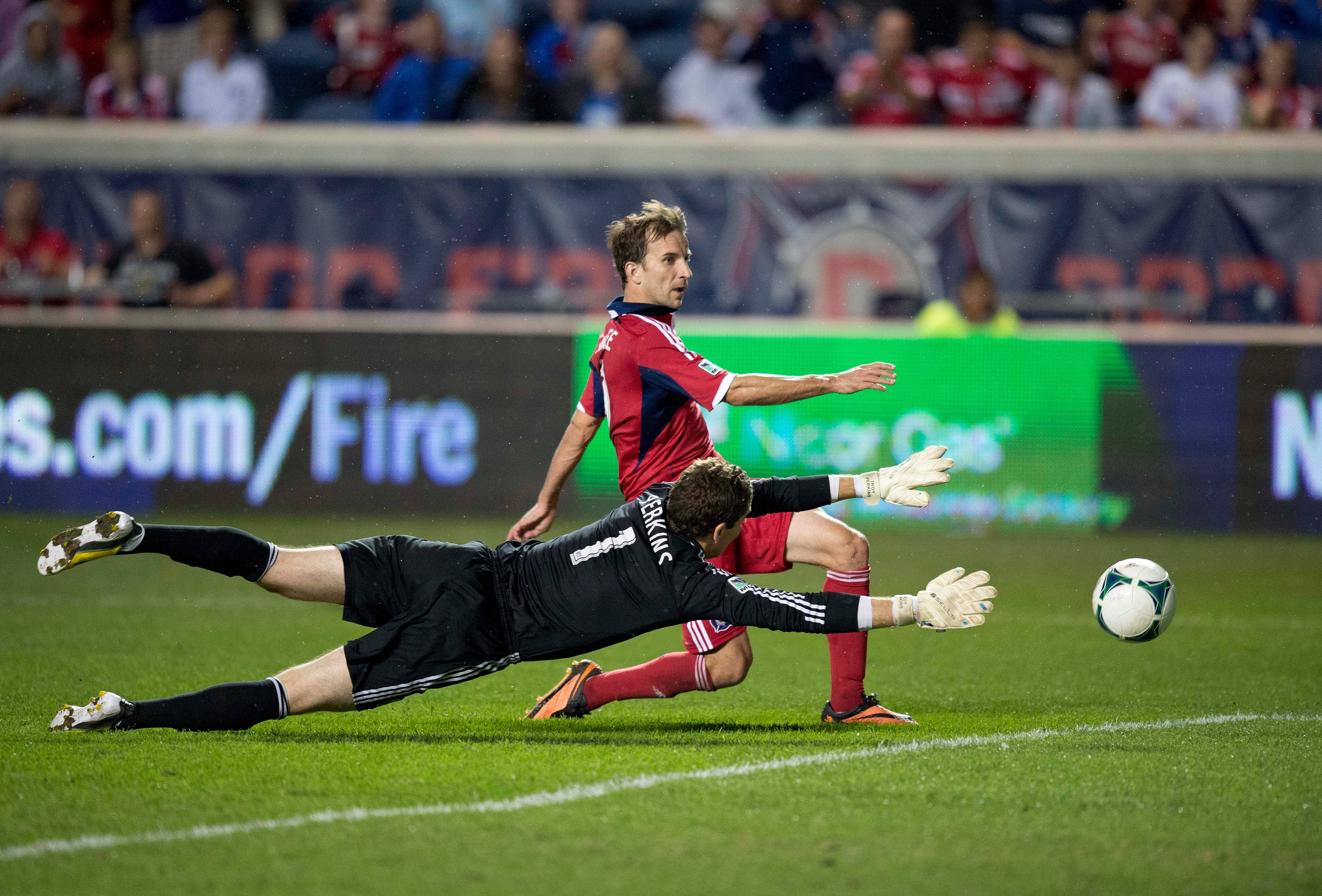 In this photo provided by the Chicago Fire, forward Mike Magee, left, scores past Montreal Impact goalkeeper Troy Perkins during a game last September.