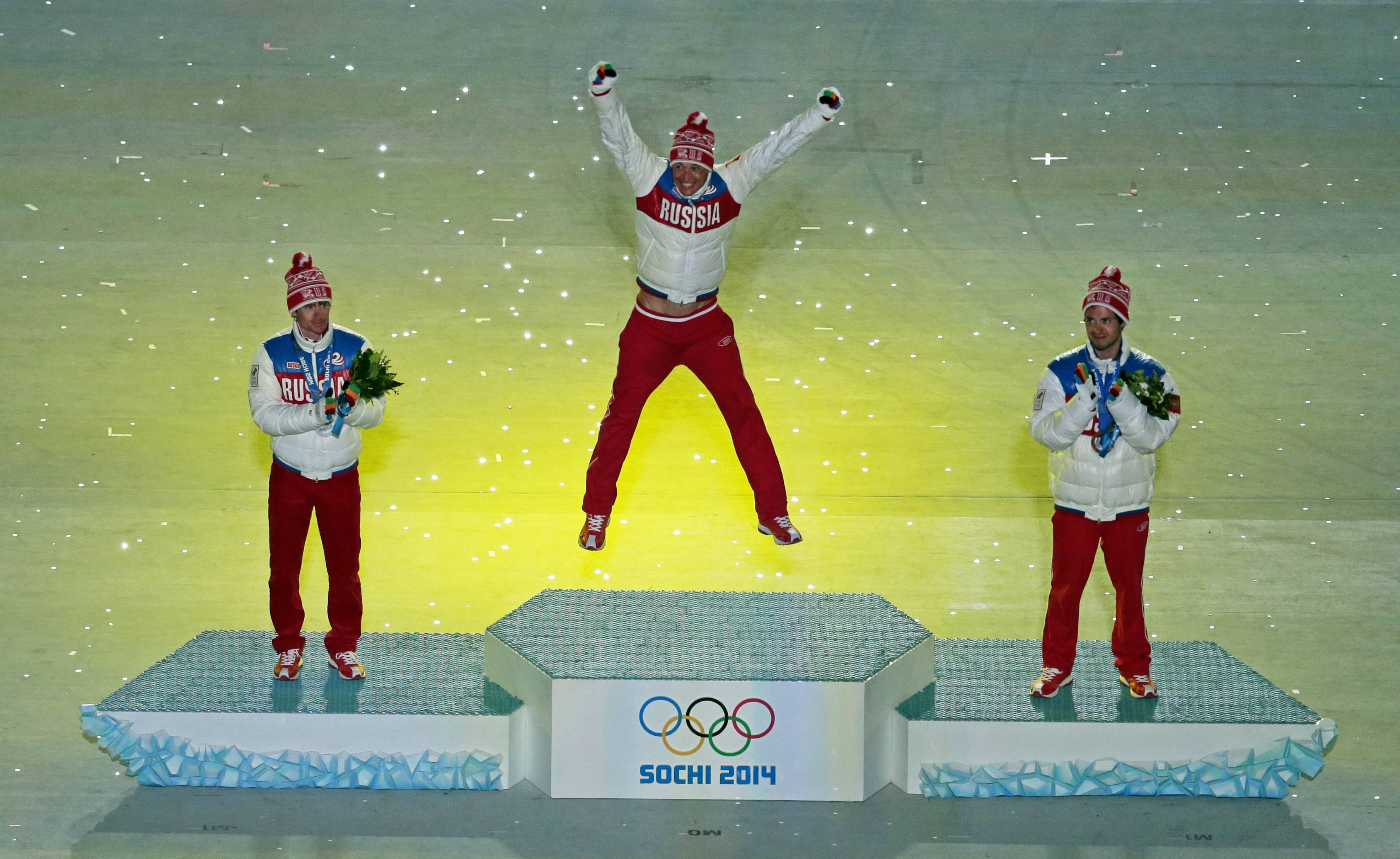 Russia's gold medal winner Alexander Legkov, center, with compatriots silver medal winner Maxim Vylegzhanin, left, and bronze medal winner Ilia Chernousov during the medal ceremony for the men's 50-kilometer cross-country race during the closing ceremony of the 2014 Winter Olympics, Sunday, Feb. 23, 2014, in Sochi, Russia.