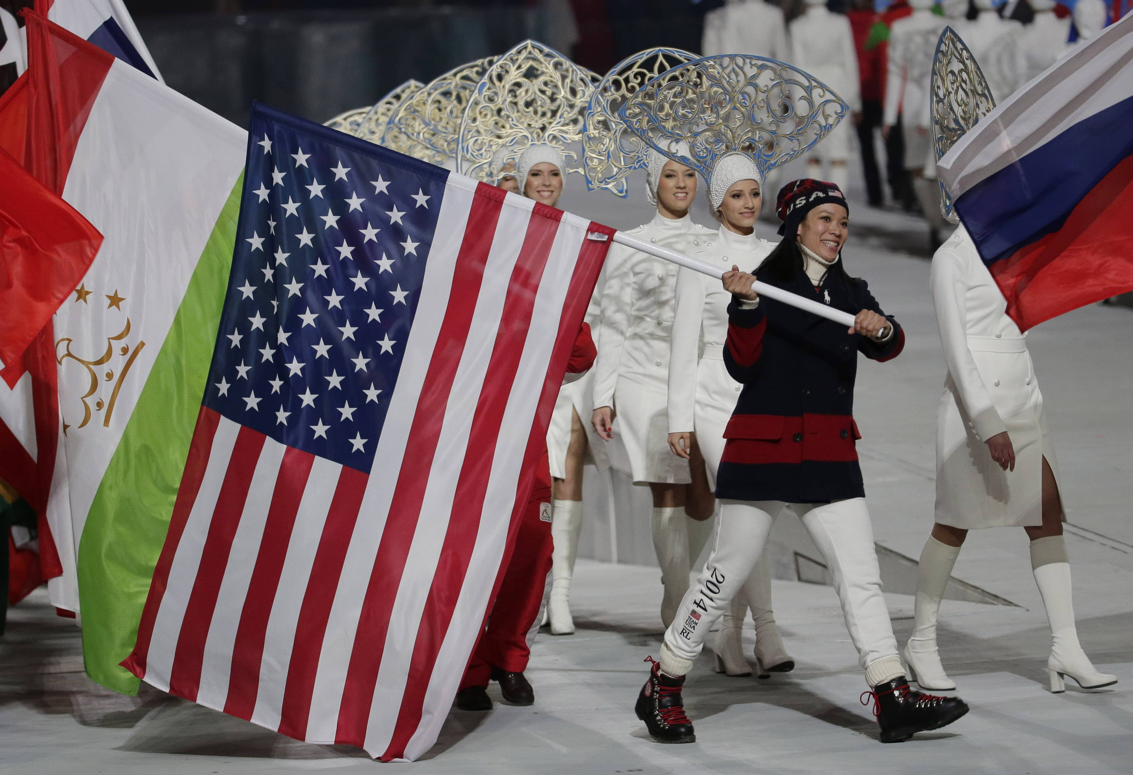 United States' Julie Chu carries her nation's flag while participating in the closing ceremony of the 2014 Winter Olympics, Sunday, Feb. 23, 2014, in Sochi, Russia.