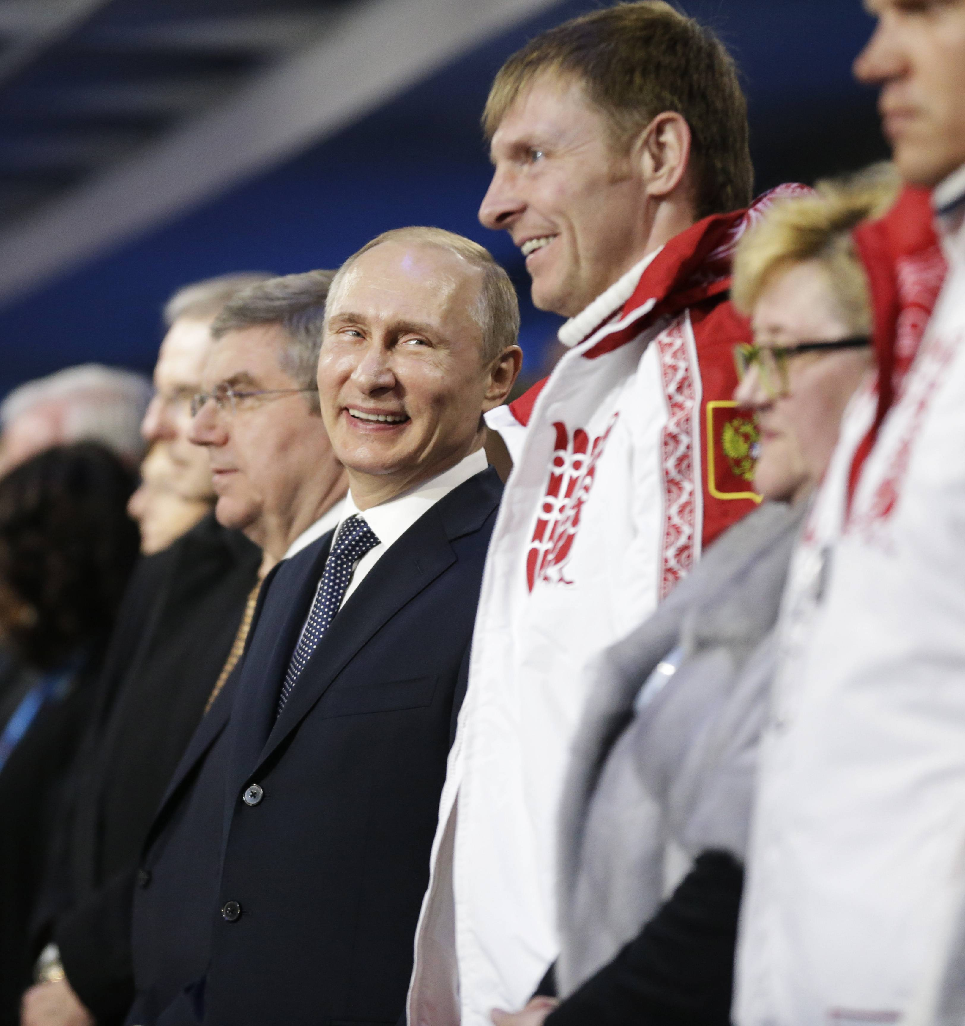 Russian President Vladimir Putin, left, stands next to Alexander Zubkov, gold medalist in the two-man and four-man bobsled for Russia, during the closing ceremony of the 2014 Winter Olympics, Sunday, Feb. 23, 2014, in Sochi, Russia.