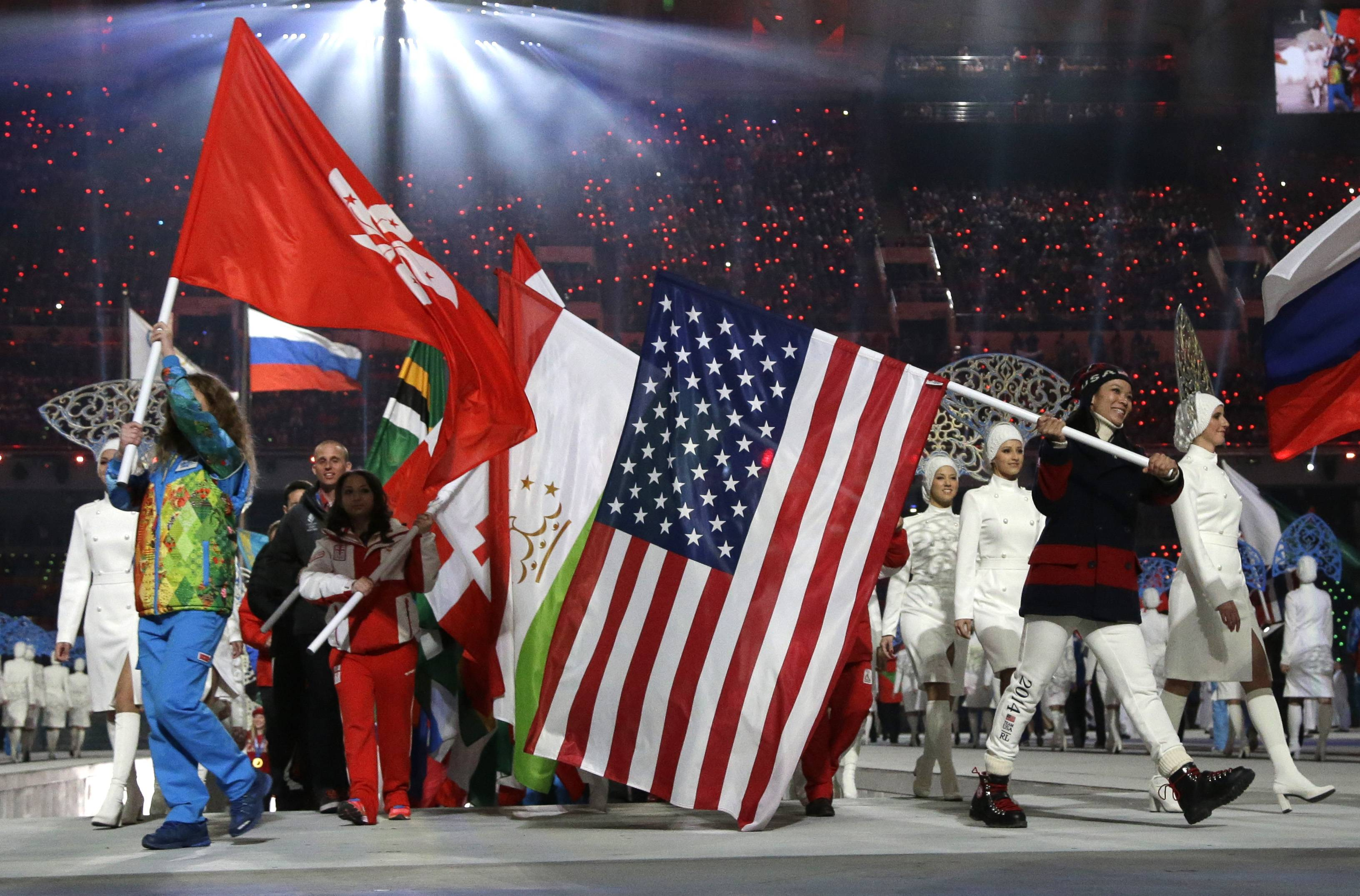 United States' Julie Chu, right, carries the flag during the closing ceremony of the 2014 Winter Olympics, Sunday, Feb. 23, 2014, in Sochi, Russia.