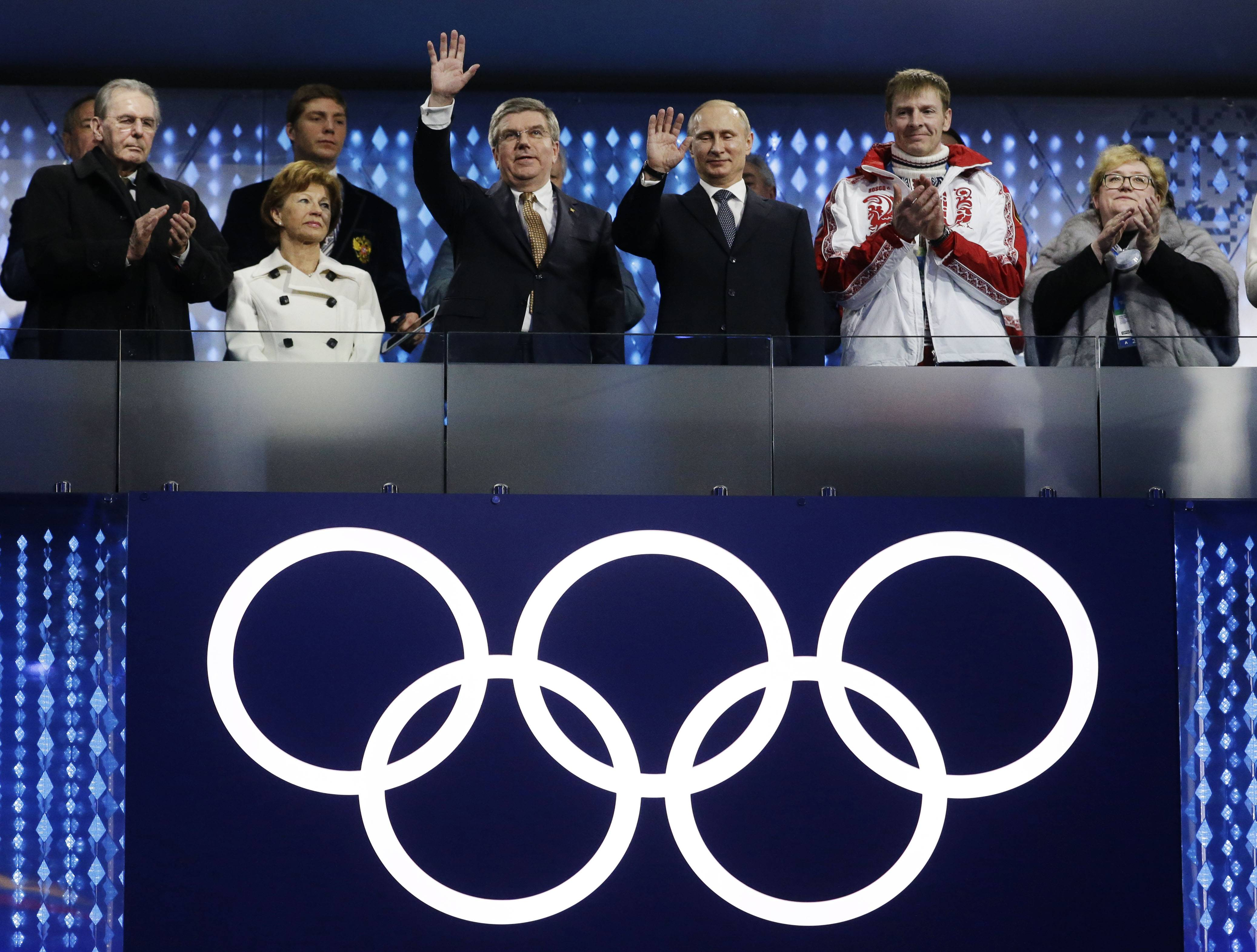 International Olympic Committee (IOC) President Thomas Bach, third from left, and Russian President Vladimir Putin, third from right, wave to spectators during the closing ceremony of the 2014 Winter Olympics, Sunday, Feb. 23, 2014, in Sochi, Russia. At far left is former IOC President Jacques Rogge.