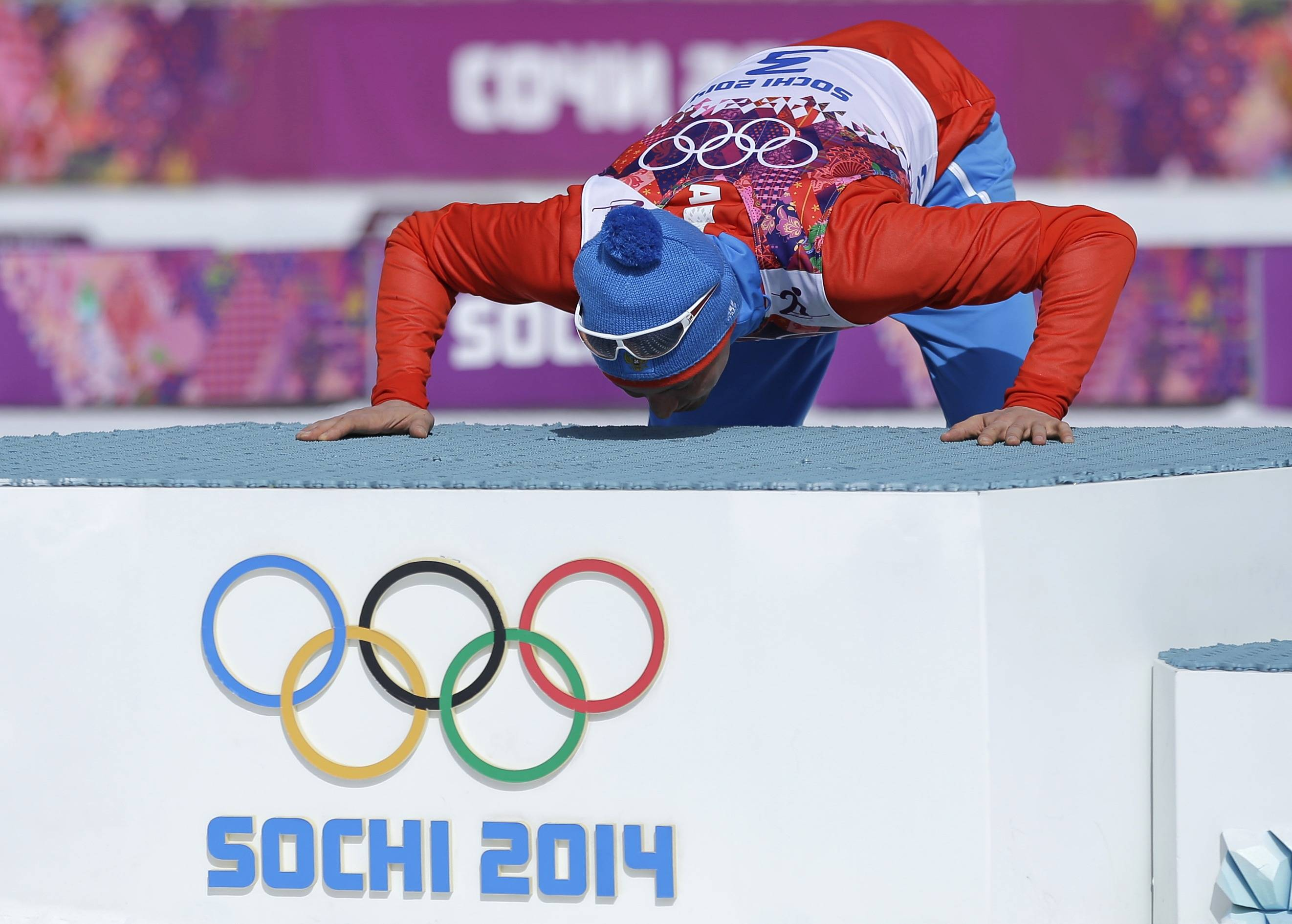 Russia's Alexander Legkov kisses the podium during the flower ceremony after winning the gold medal in the men's 50K cross-country race at the 2014 Winter Olympics, Sunday, Feb. 23, 2014, in Krasnaya Polyana, Russia.