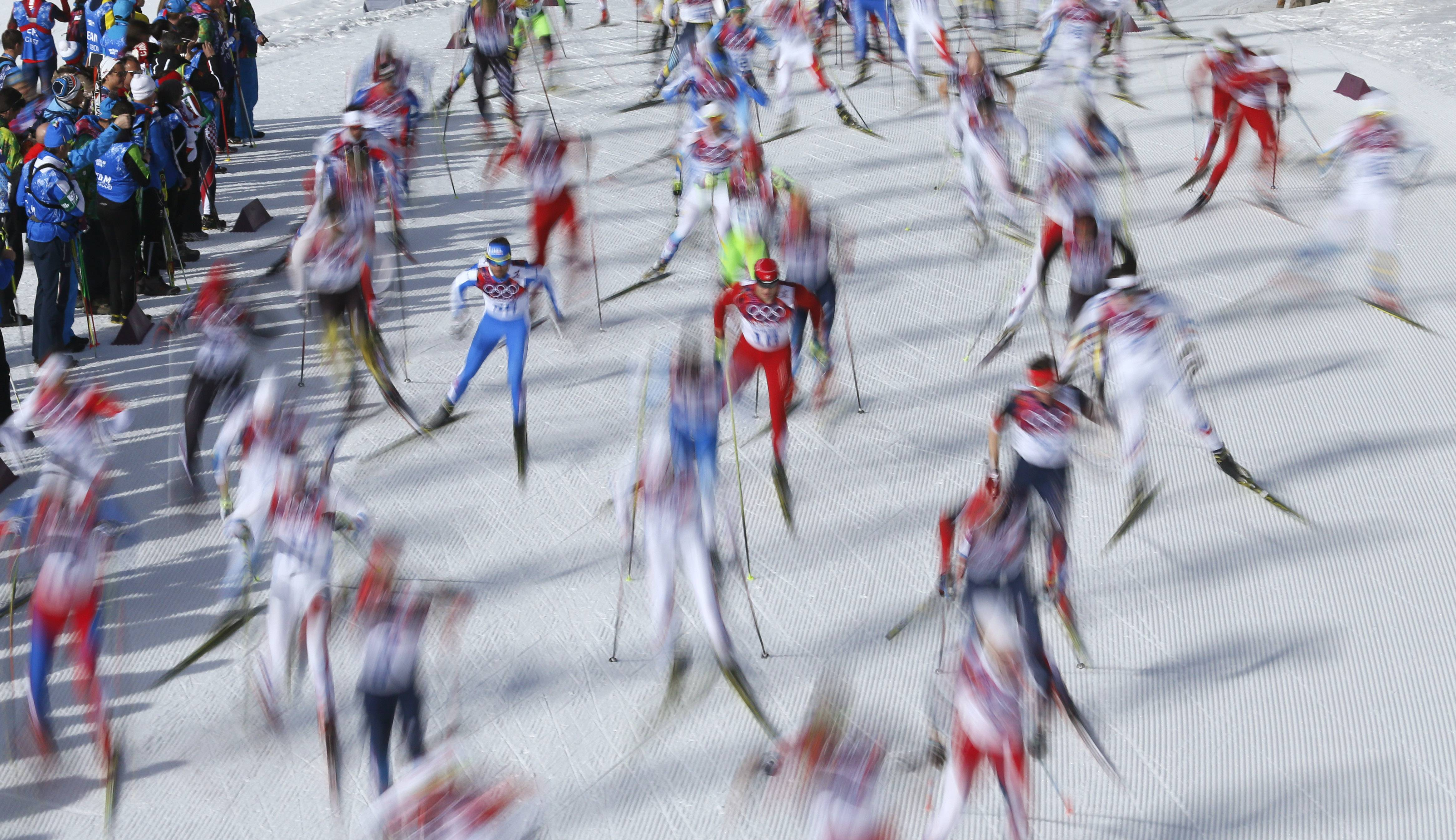 In this photo taken with slow shutter speed Switzerland's Dario Cologna, center, skis during the men's 50K cross-country race at the 2014 Winter Olympics, Sunday, Feb. 23, 2014, in Krasnaya Polyana, Russia.