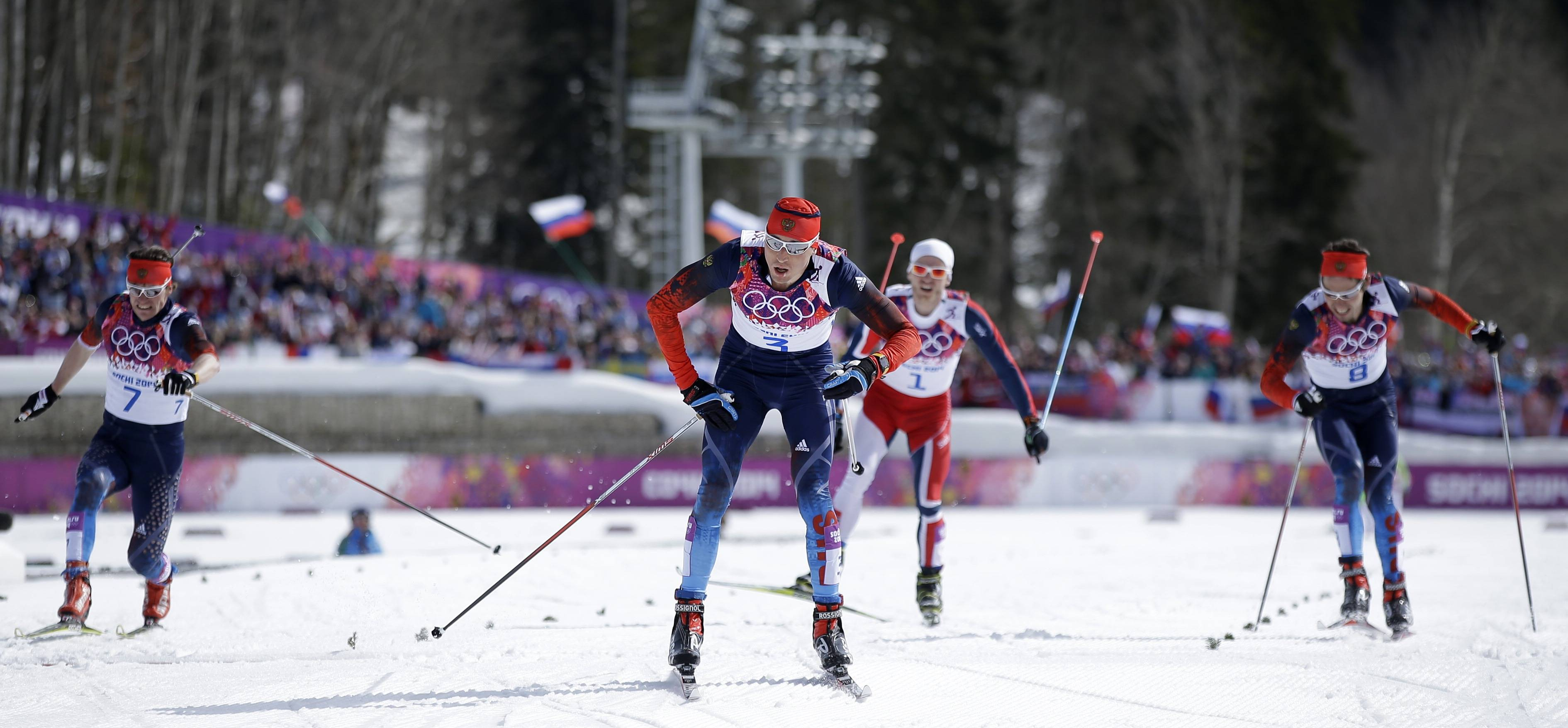 Russia's gold medal winner Alexander Legkov, center, crosses the finish line ahead of Russia's silver medal winner Maxim Vylegzhanin, left, and Russia's bronze medal winner Ilia Chernousov, right, in the men's 50K cross-country race at the 2014 Winter Olympics, Sunday, Feb. 23, 2014, in Krasnaya Polyana, Russia.