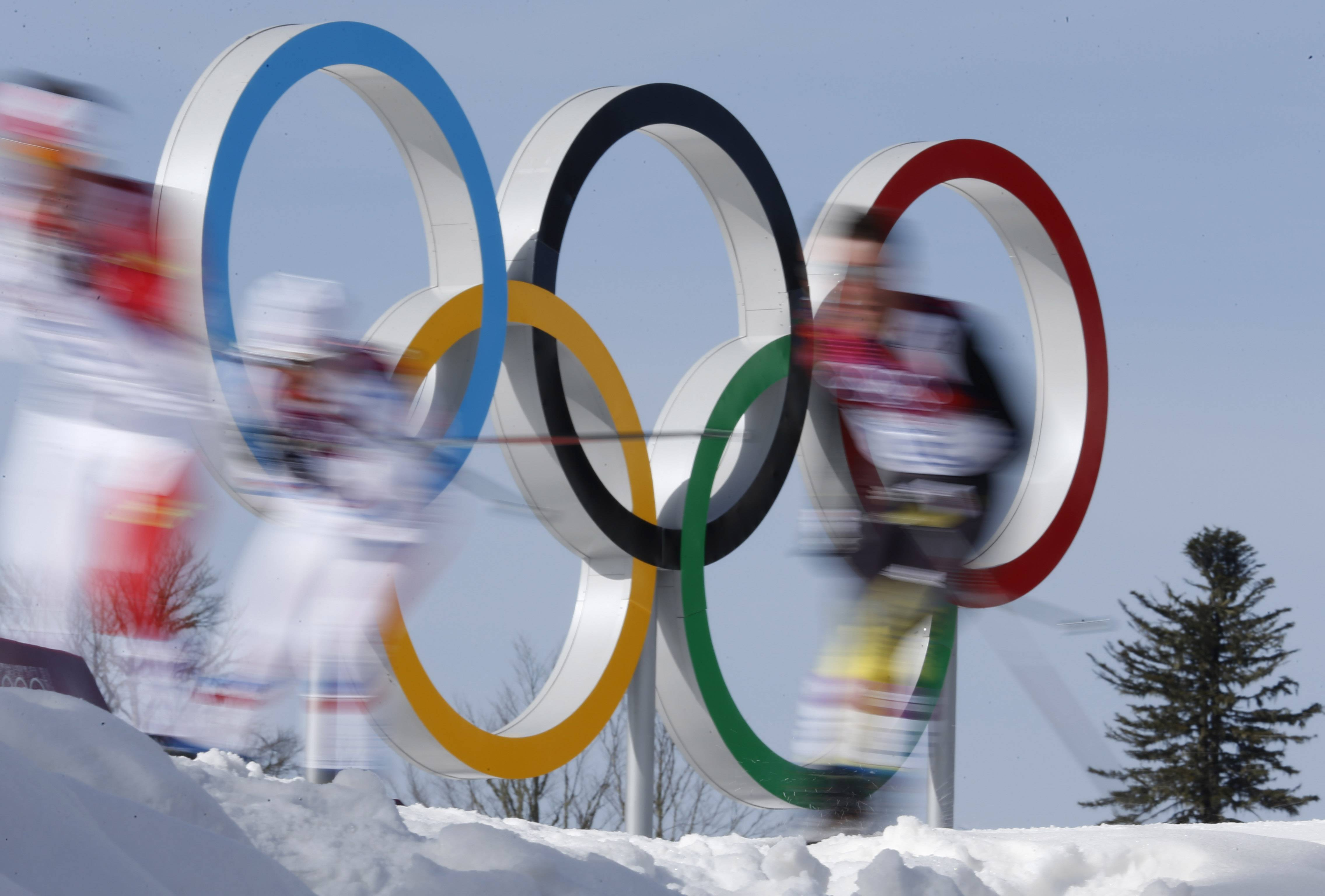 In this photo taken with slow shutter speed athletes pass by the Olympic rings during the men's 50K cross-country race at the 2014 Winter Olympics, Sunday, Feb. 23, 2014, in Krasnaya Polyana, Russia.