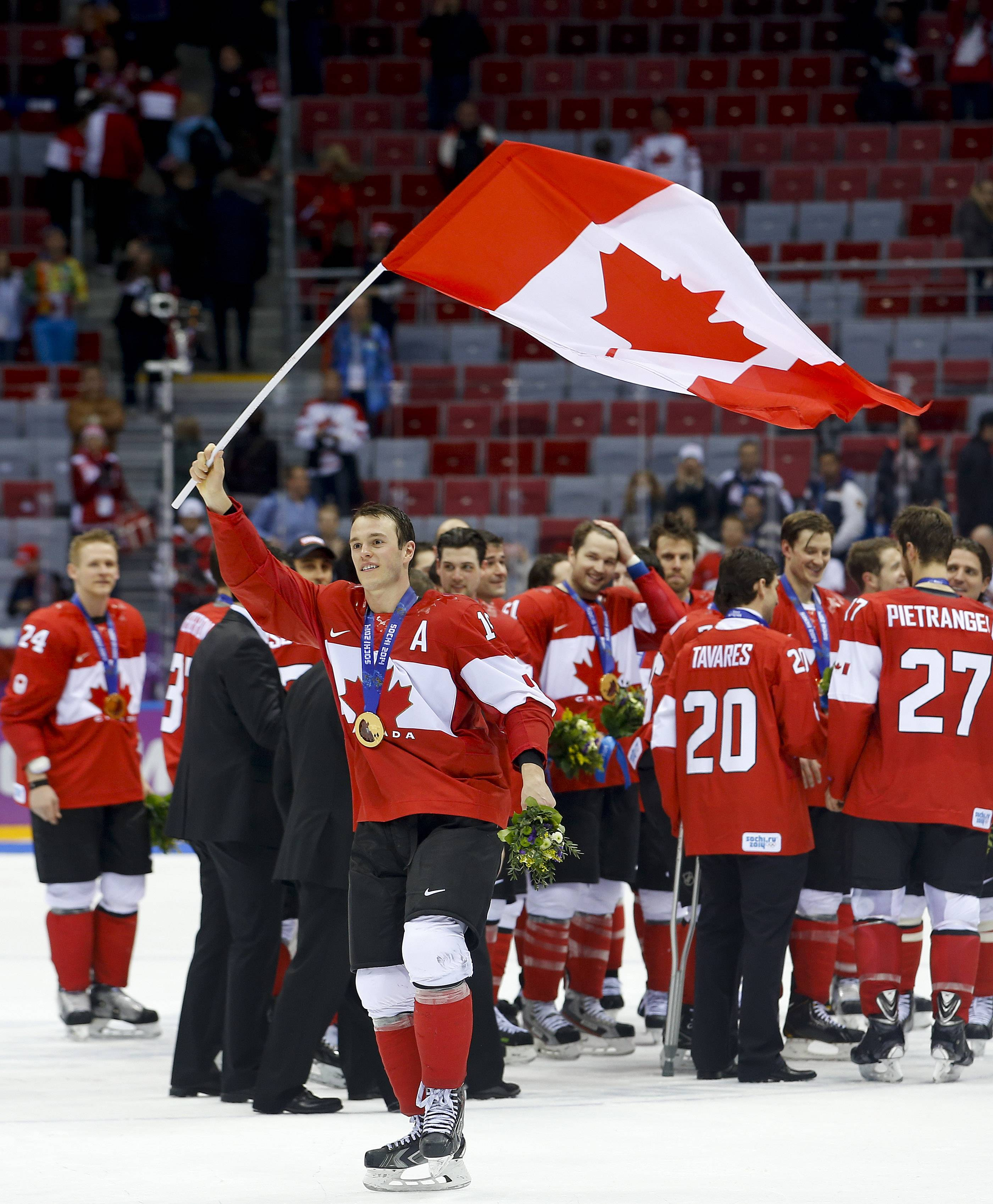 Canada forward Jonathan Toews waves the Canadian flag after Canada beat Sweden 3-0 in the men's gold medal ice hockey game at the 2014 Winter Olympics, Sunday, Feb. 23, 2014, in Sochi, Russia.