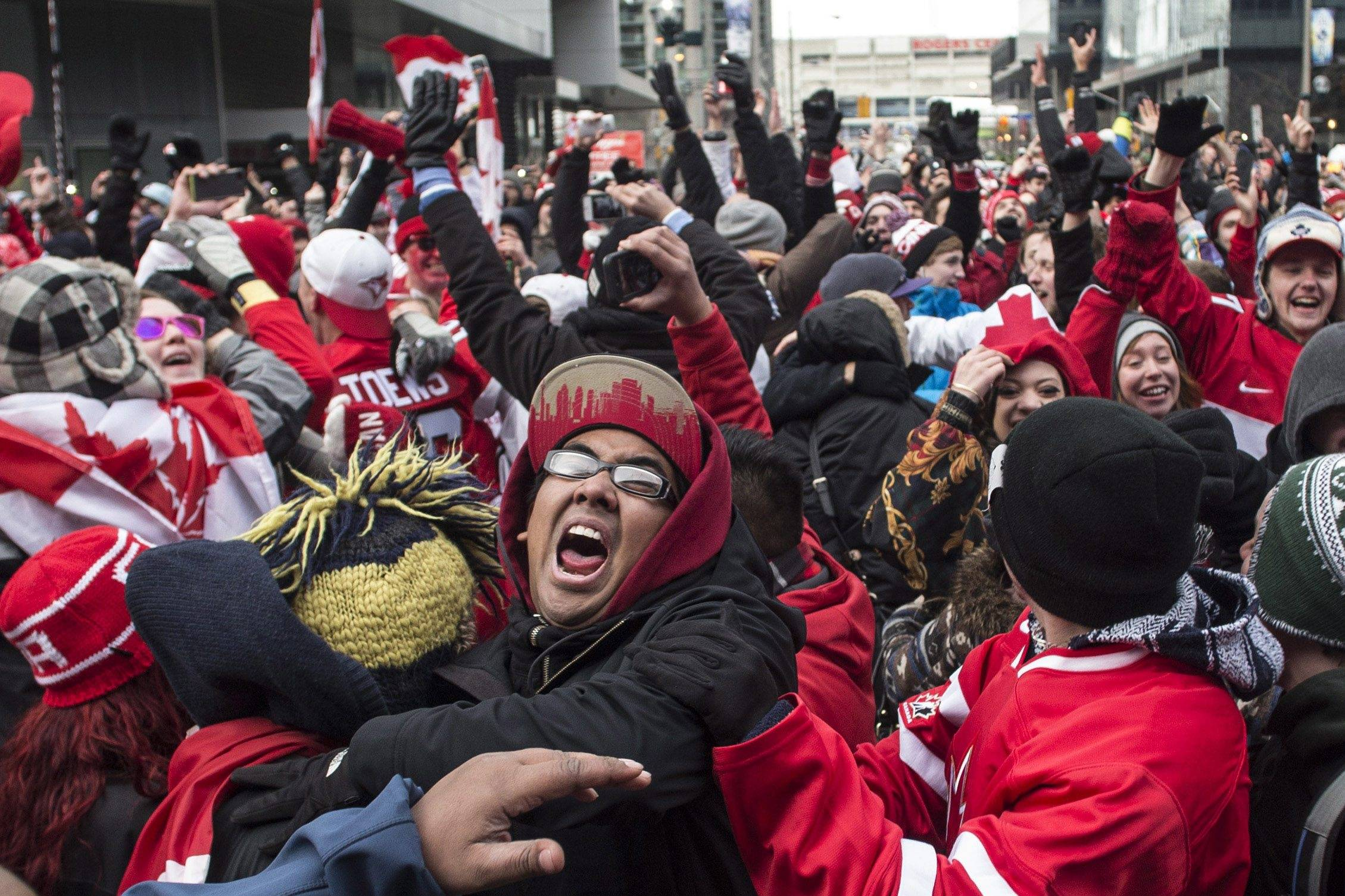 Hockey fans celebrate in Toronto's Maple Leaf Square in Toronto after the final buzzer as Canada beat Sweden 3-0 to win the Gold Medal in the men's Olympic Hockey Final on Sunday, Feb. 23, 2014.