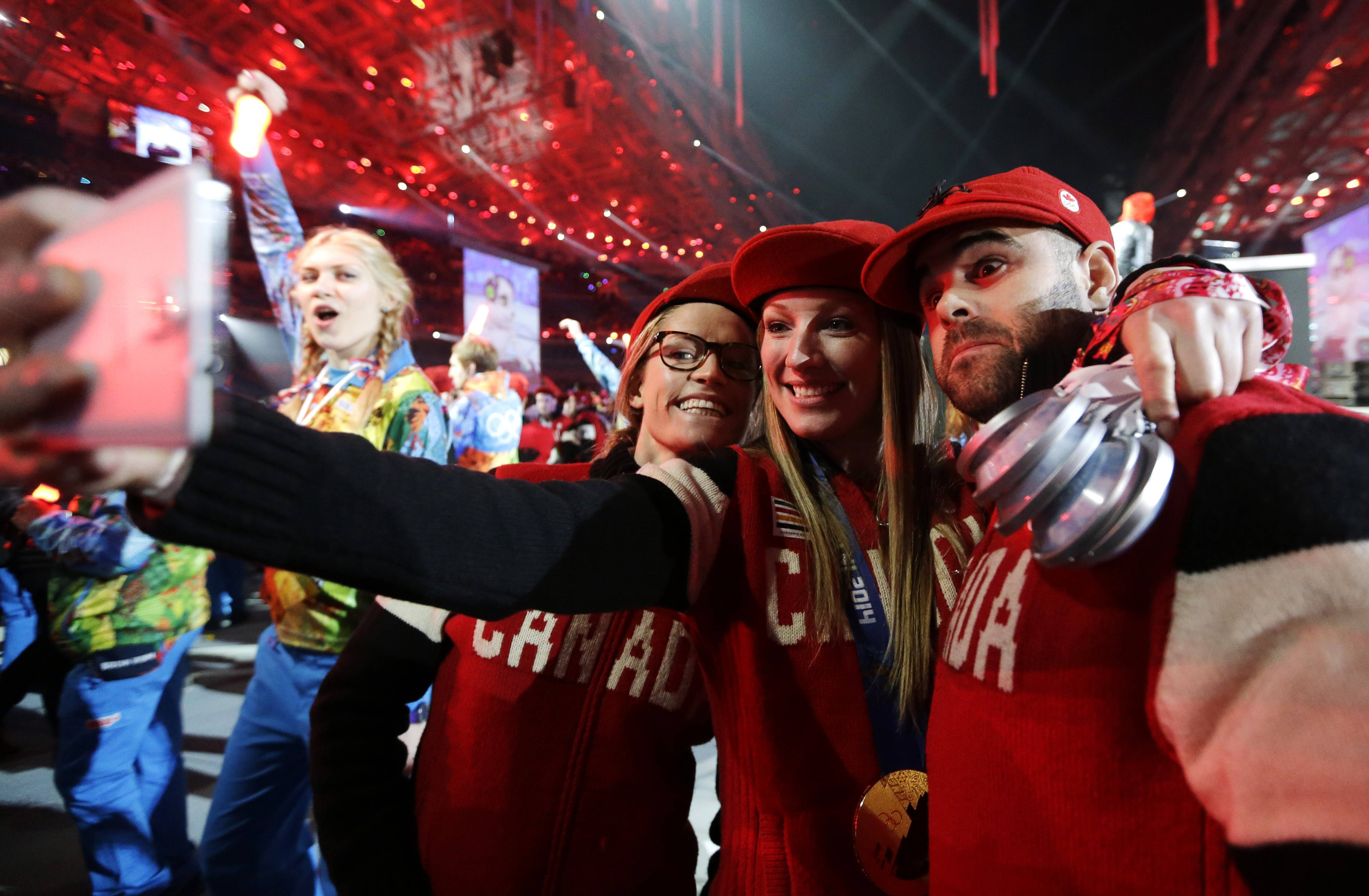 Canadian athletes take a self-portrait of themselves with a mobile phone during the closing ceremony of the 2014 Winter Olympics, Sunday, Feb. 23, 2014, in Sochi, Russia.