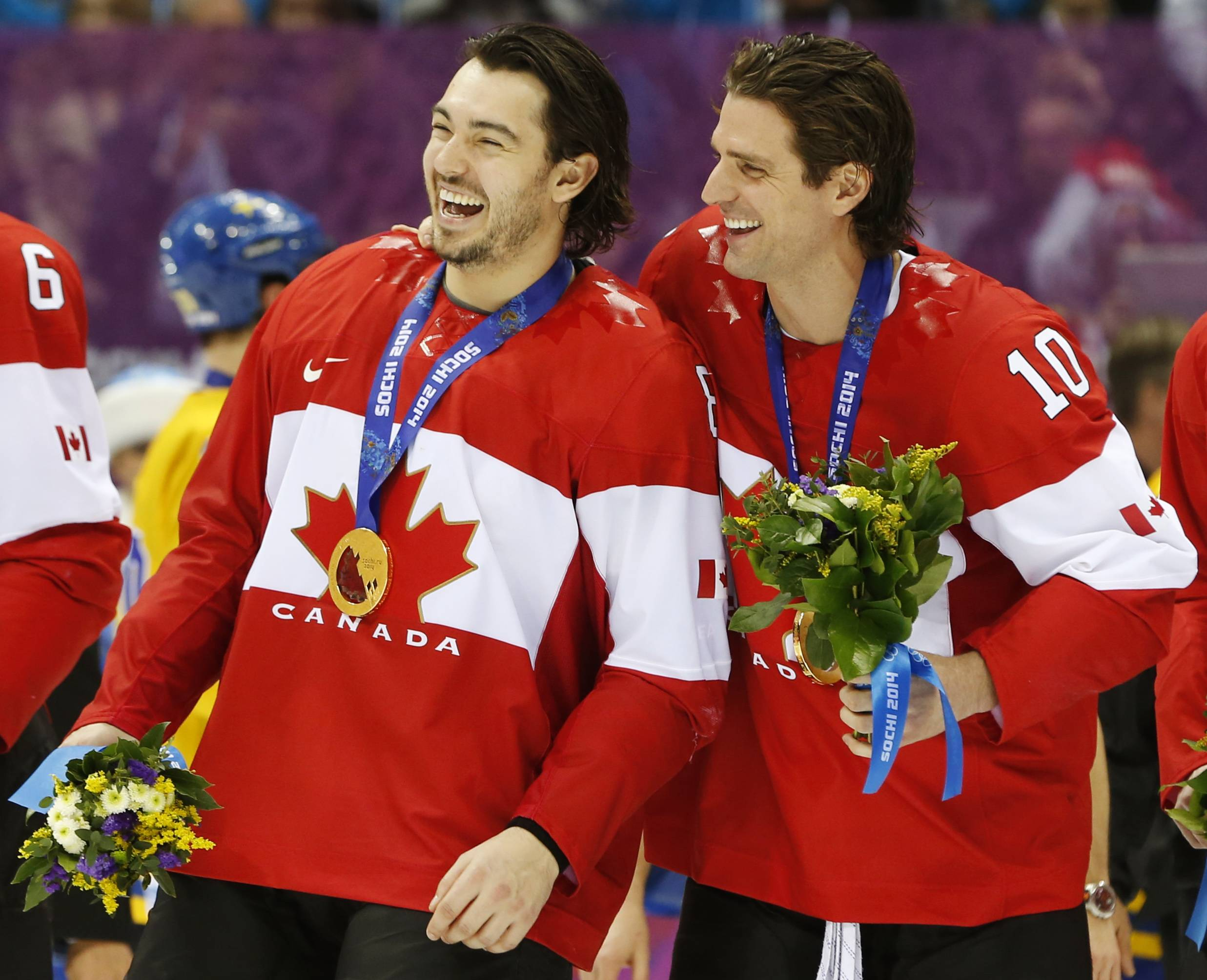 Drew Doughty of Canada (8) and Patrick Sharp of Canada (10) skate with their gold medals after the gold medal men's ice hockey game at the 2014 Winter Olympics, Sunday, Feb. 23, 2014, in Sochi, Russia. Canada defeated Sweden 3-0 to win the gold medal in the tournament.