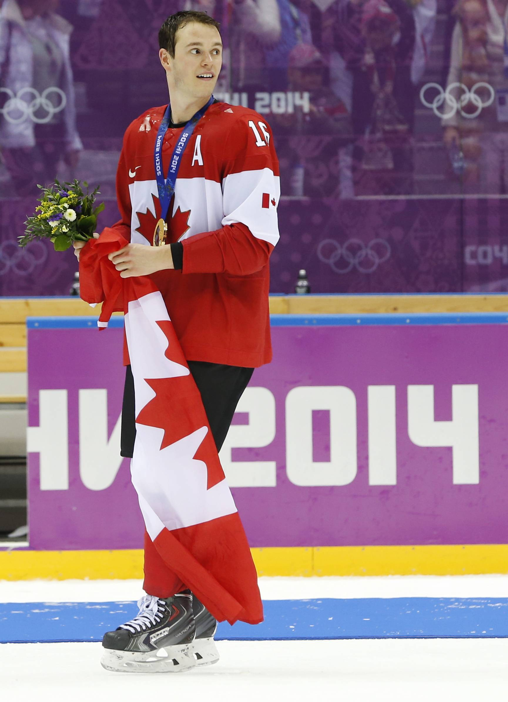 Jonathan Toews of Canada (16) skates with the Canadian flag after the gold medal men's ice hockey game at the 2014 Winter Olympics, Sunday, Feb. 23, 2014, in Sochi, Russia. Canada defeated Sweden 3-0 to win the gold medal.