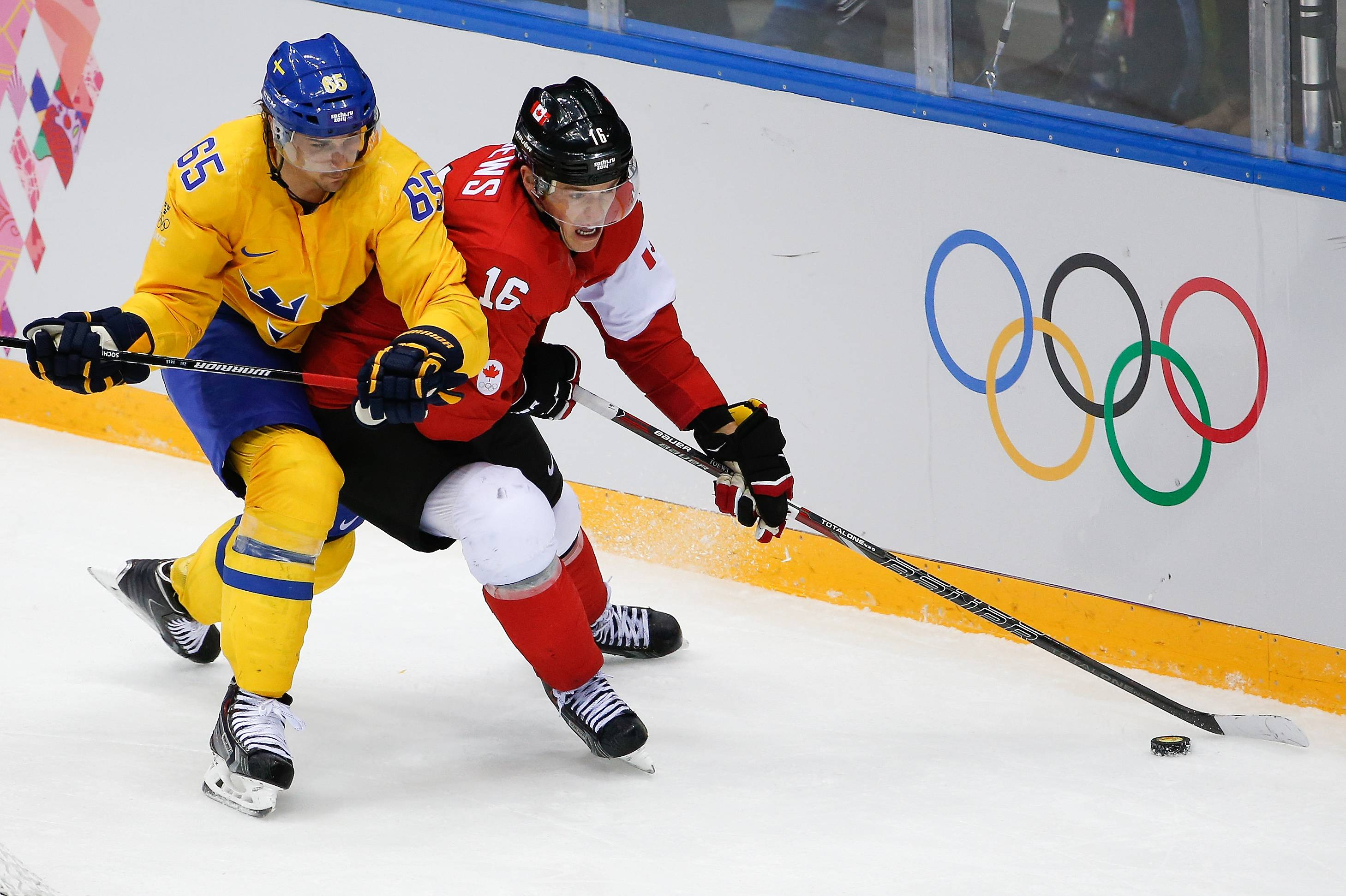 Jonathan Toews of Canada (16) tales control of the puck under pressure from Erik Karlsson of Sweden (65) during the third period of the men's gold medal ice hockey game at the 2014 Winter Olympics, Sunday, Feb. 23, 2014, in Sochi, Russia.