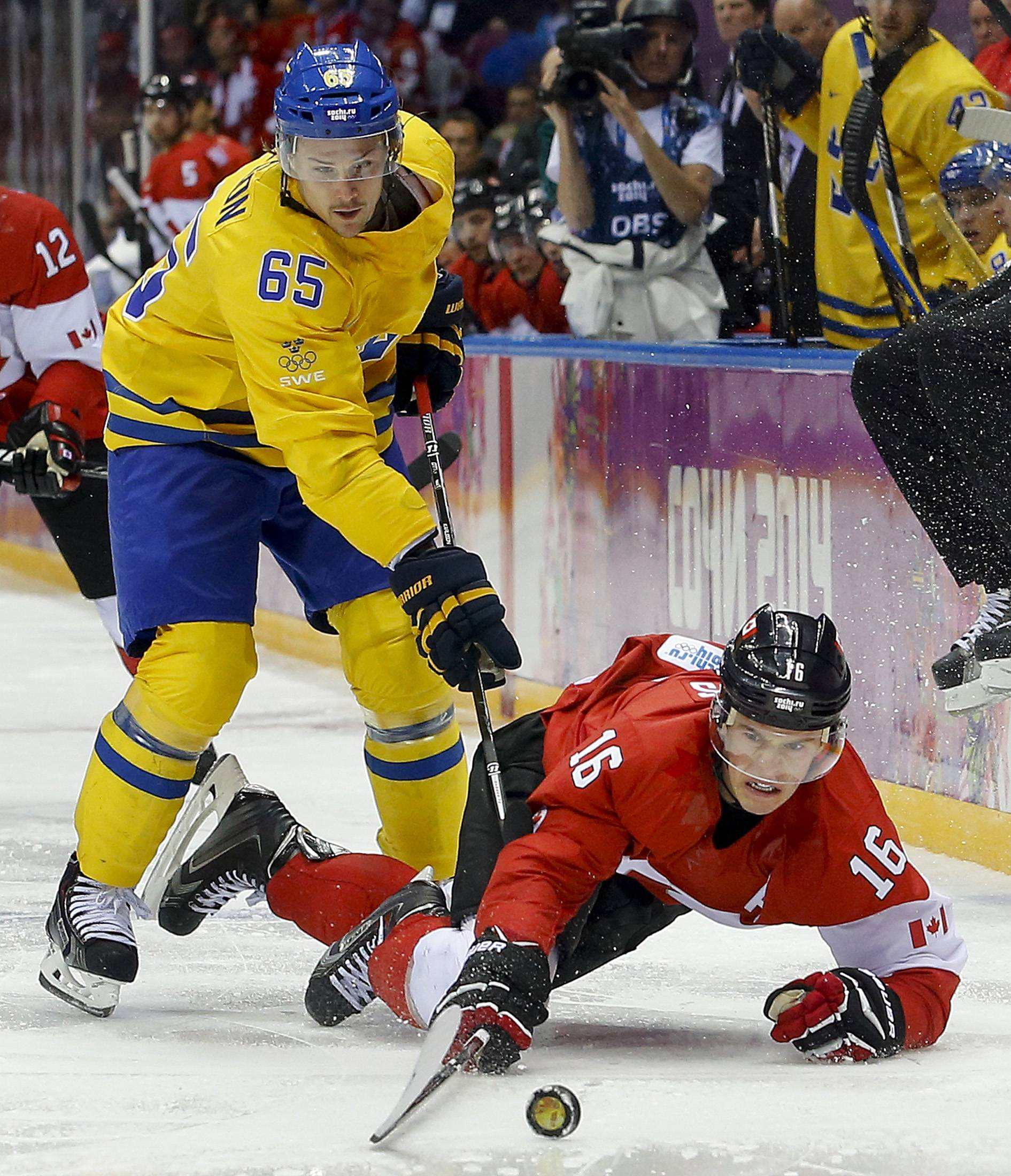 Canada forward Jonathan Toews dives after the puck against Sweden defenseman Erik Karlsson during the third period of the men's gold medal ice hockey game at the 2014 Winter Olympics, Sunday, Feb. 23, 2014, in Sochi, Russia.
