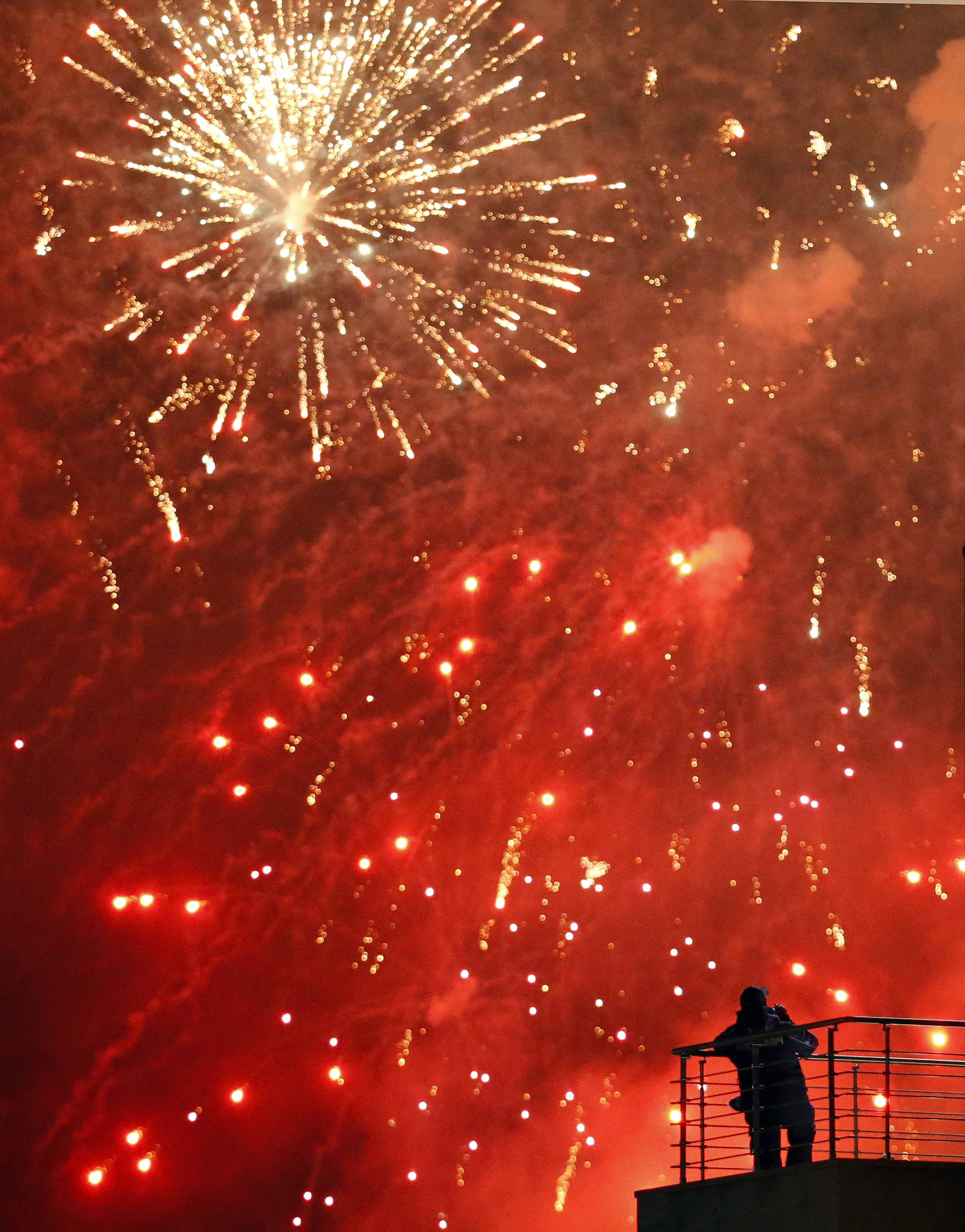A man watches fireworks from a balcony during the closing ceremonies at the 2014 Winter Olympics, Sunday, Feb. 23, 2014, in Sochi, Russia.