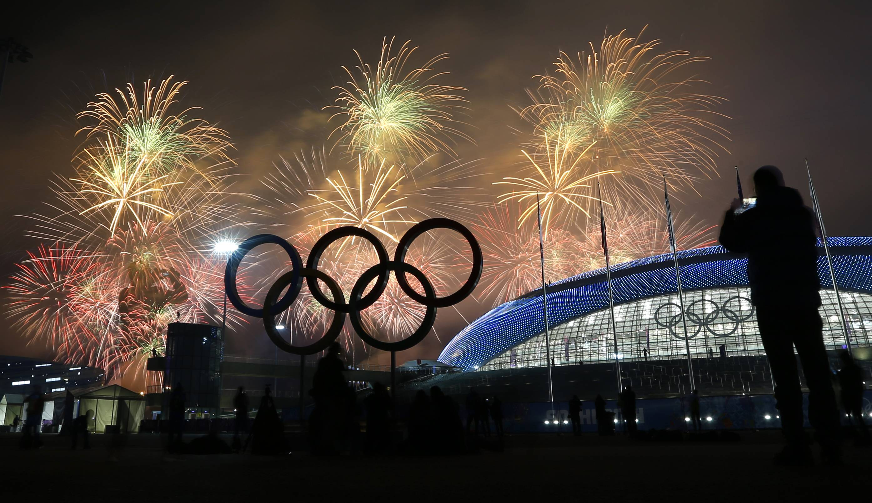 Man takes a photograph of fireworks during the closing ceremony of the 2014 Winter Olympics, Sunday, Feb. 23, 2014, in Sochi, Russia.