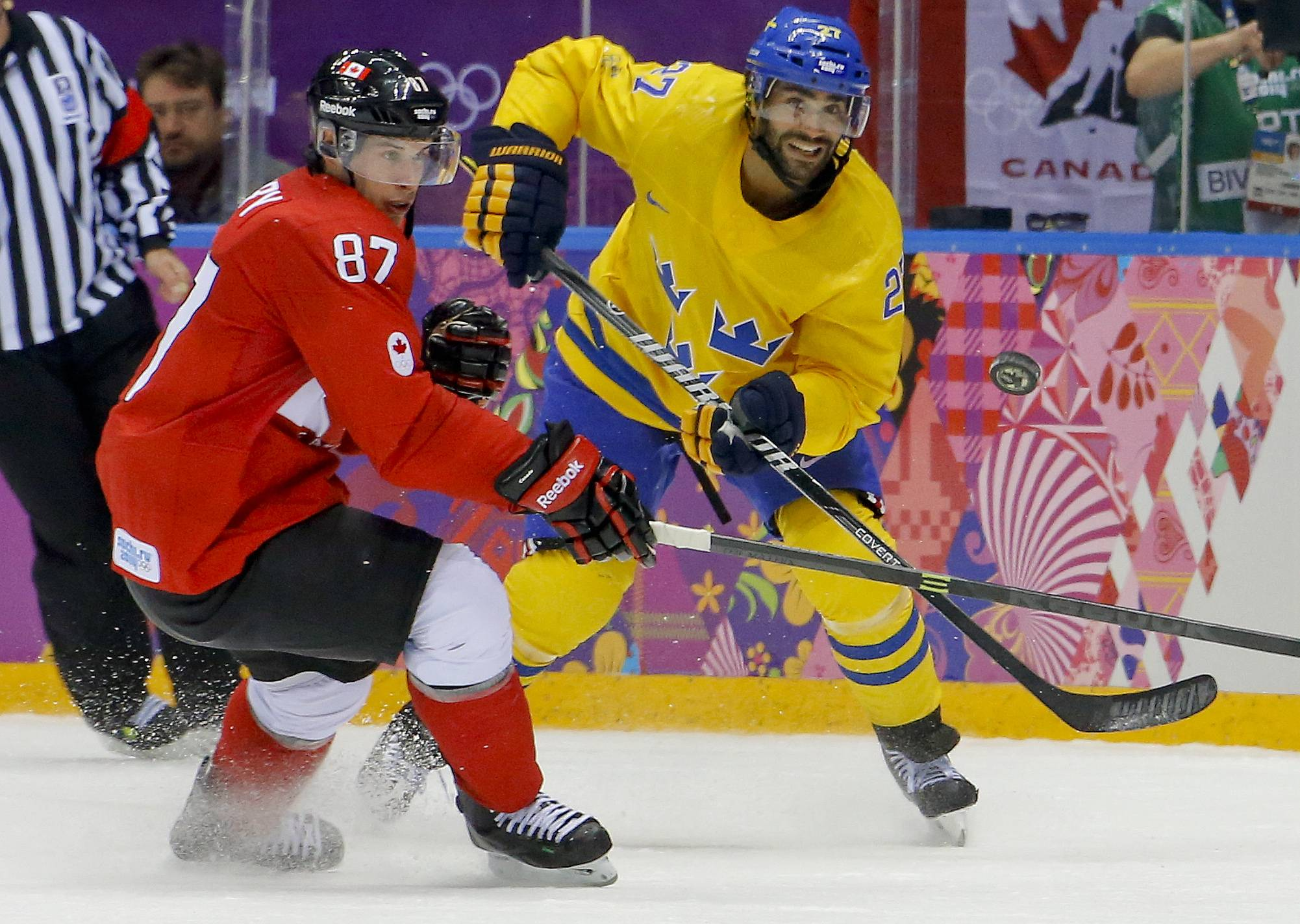 Canada forward Sidney Crosby, left, controls the puck against Sweden defenseman Johnny Oduya during the second period of the men's gold medal ice hockey game at the 2014 Winter Olympics, Sunday, Feb. 23, 2014, in Sochi, Russia.