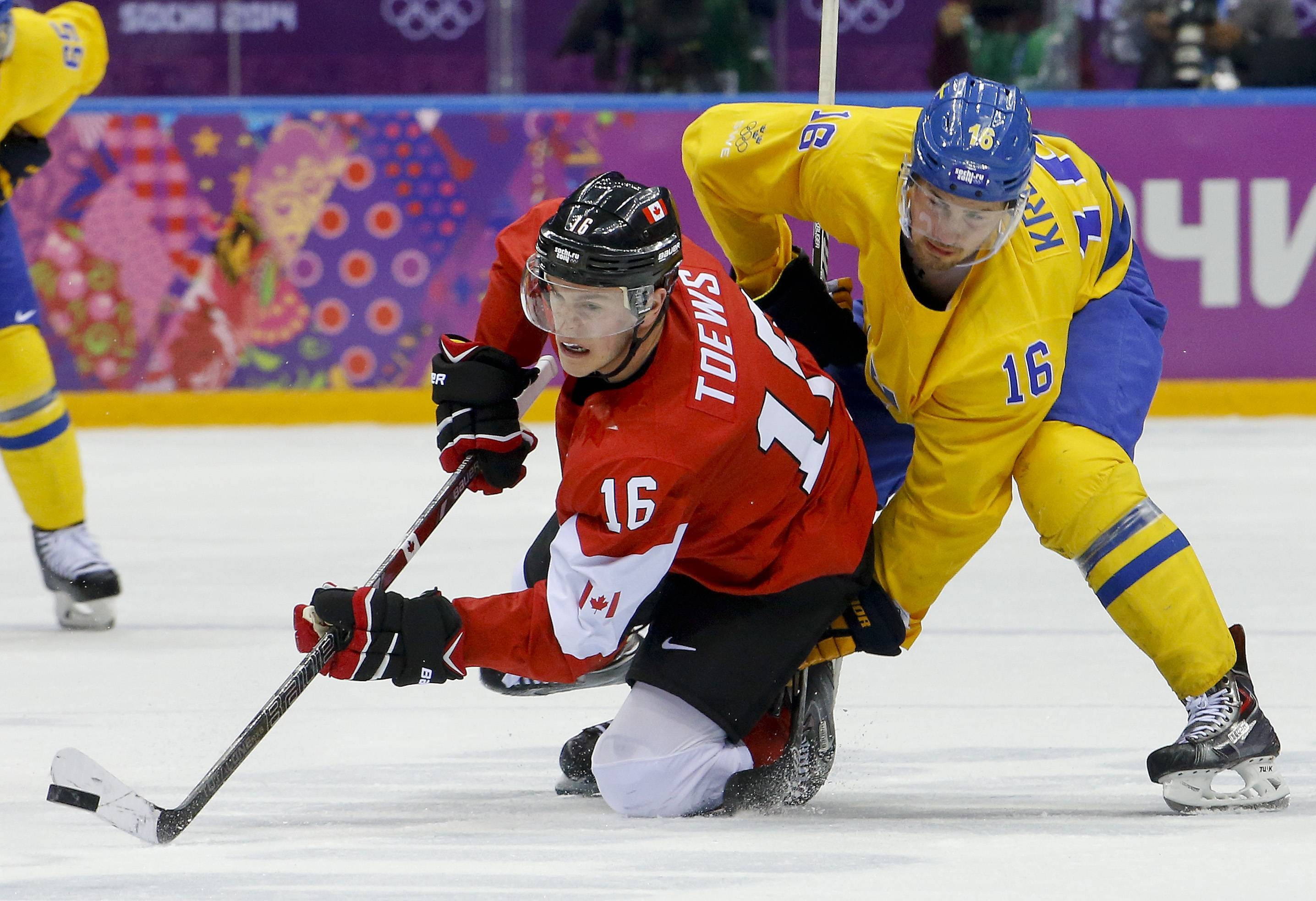 Canada forward Jonathan Toews gets a pass off against Sweden forward Marcus Kruger during the second period of the men's gold medal ice hockey game at the 2014 Winter Olympics, Sunday, Feb. 23, 2014, in Sochi, Russia.