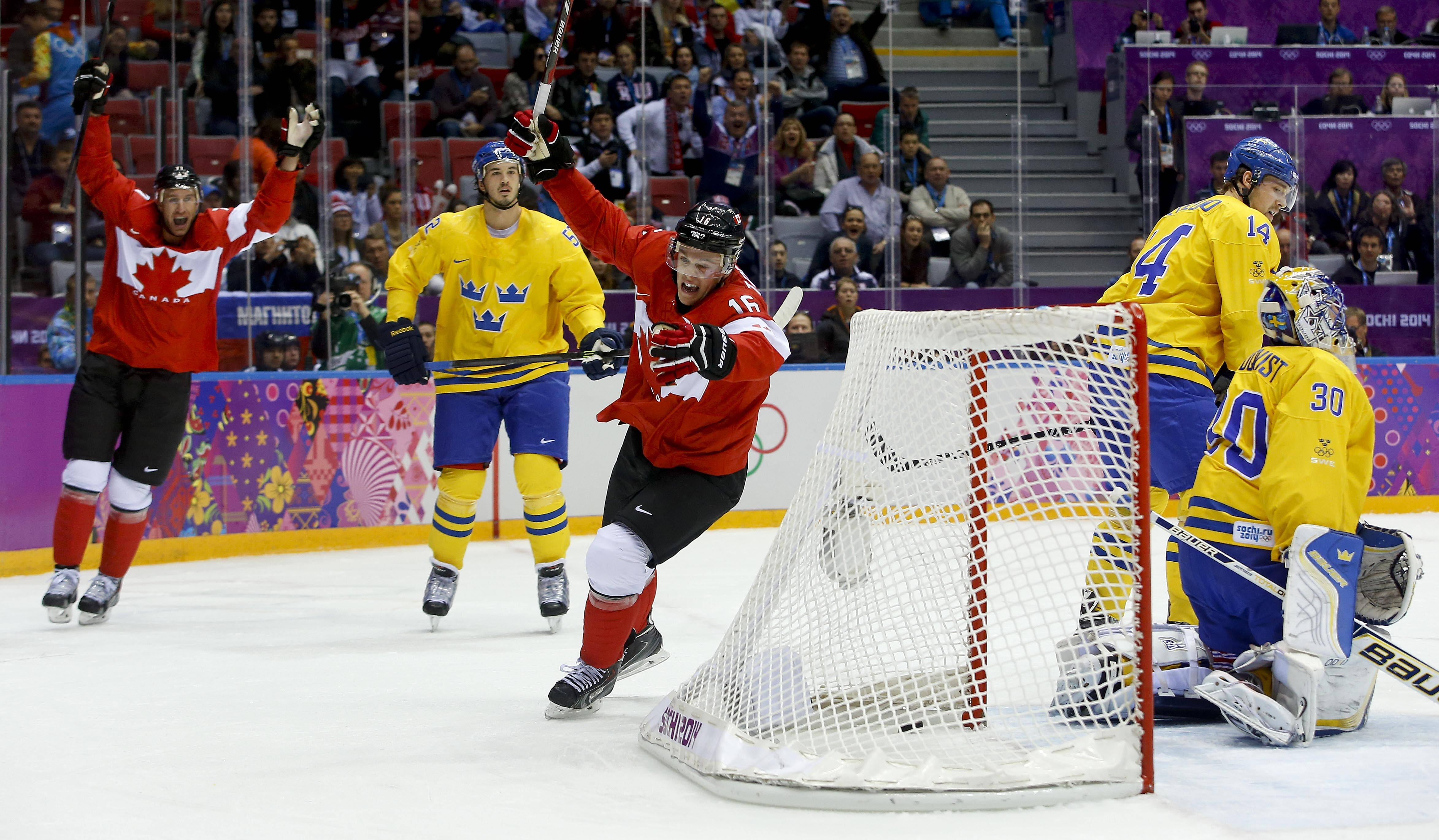 Canada forward Jonathan Toews, center, reacts upon scoring a goal against Sweden during the first period of the men's gold medal ice hockey game at the 2014 Winter Olympics, Sunday, Feb. 23, 2014, in Sochi, Russia.