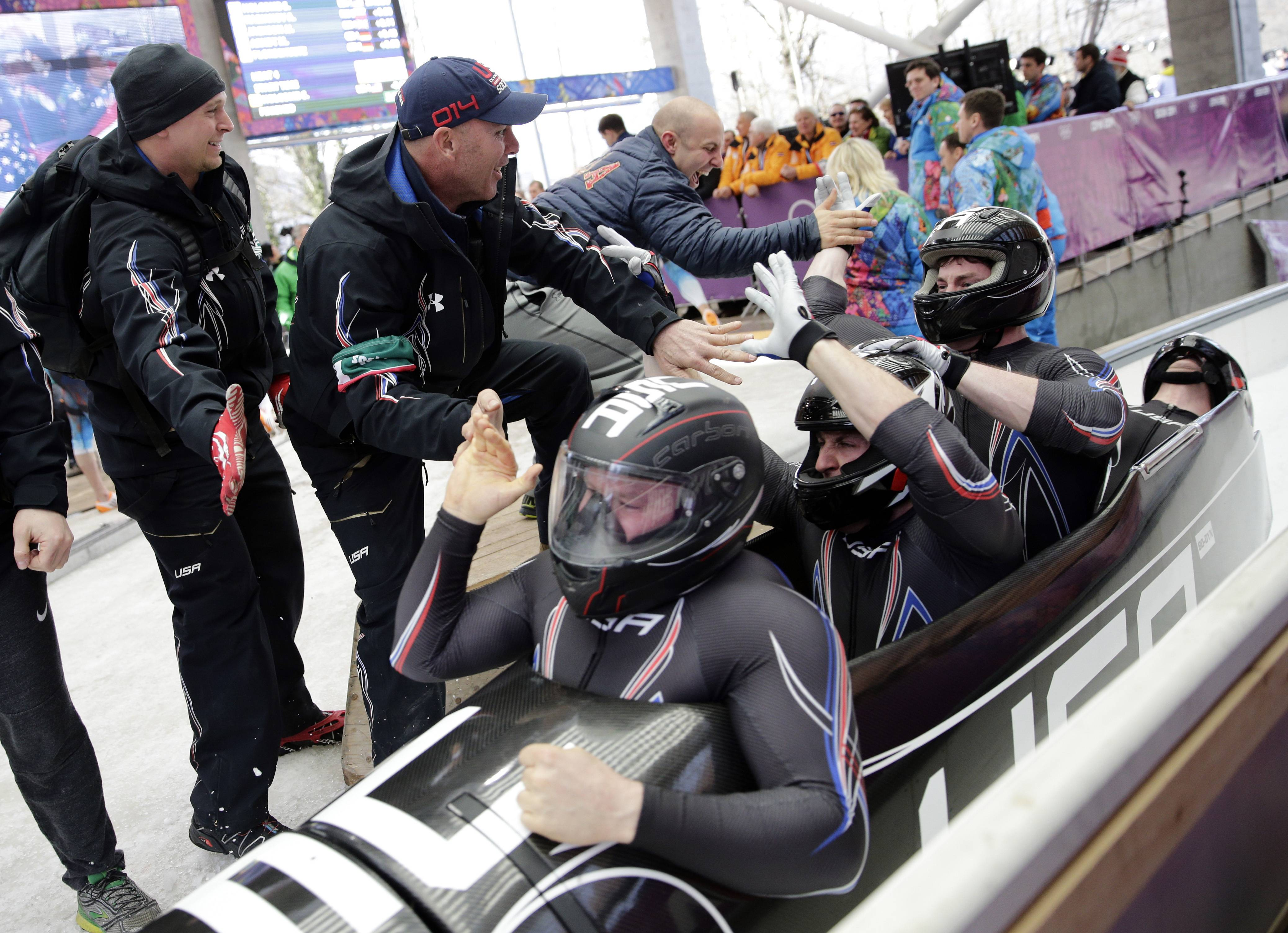 The team from the United States USA-1, with Steven Holcomb, Curtis Tomasevicz, Steven Langton and Christopher Fogt, celebrate after they won the bronze medal during the men's four-man bobsled competition final at the 2014 Winter Olympics, Sunday, Feb. 23, 2014, in Krasnaya Polyana, Russia.