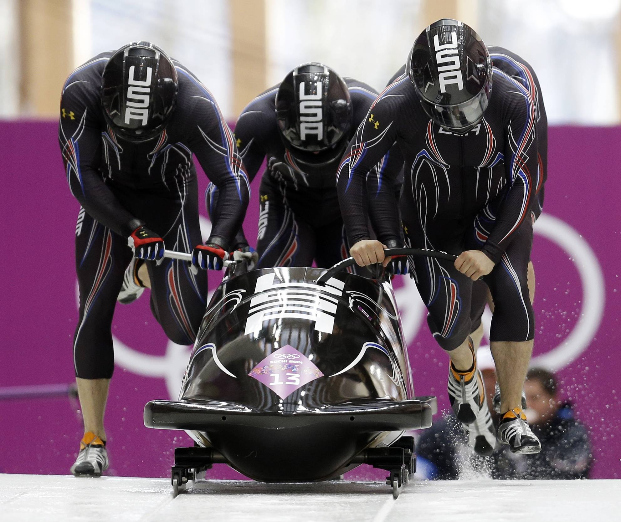 The team from the United States USA-2, with Nick Cunningham, Justin Olsen, Johnny Quinn and Dallas Robinson, start their third run during the men's four-man bobsled competition final at the 2014 Winter Olympics, Sunday, Feb. 23, 2014, in Krasnaya Polyana, Russia.