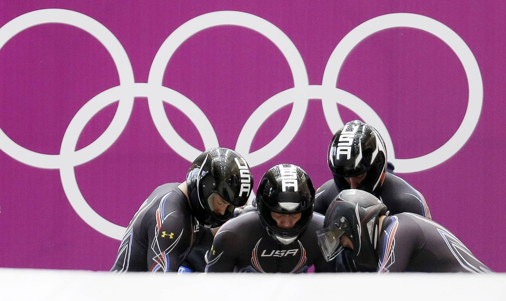 The team from the United States USA-1, with Steven Holcomb, Curtis Tomasevicz, Steven Langton and Christopher Fogt, start their third run during the men's four-man bobsled competition final at the 2014 Winter Olympics, Sunday, Feb. 23, 2014, in Krasnaya Polyana, Russia.