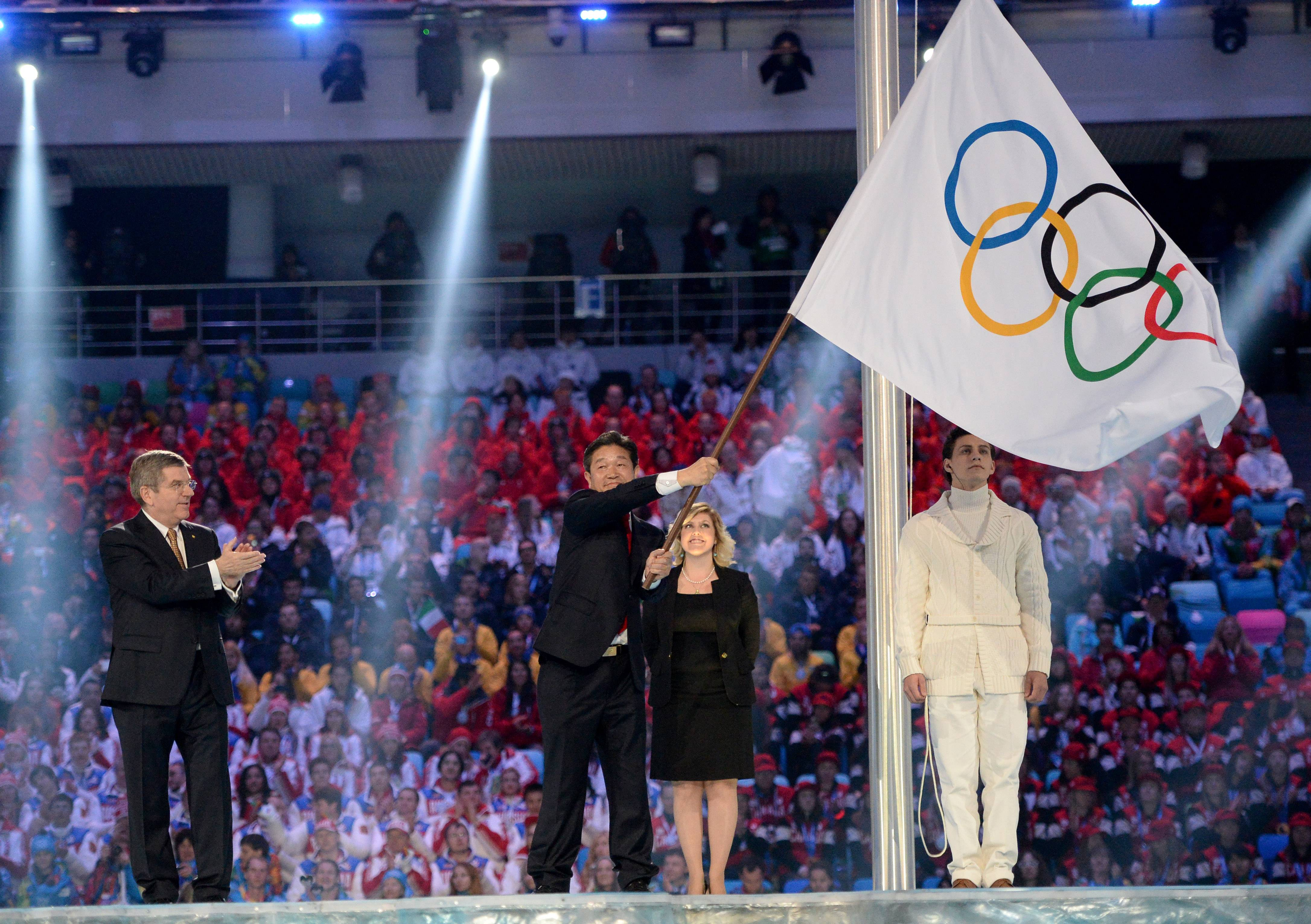 International Olympic Committee President Thomas Bach, left, applauds as Lee Seok-rai, mayor of Pyeongchang, waves the Olympic flag during the closing ceremony of the 2014 Winter Olympics, Sunday, Feb. 23, 2014, in Sochi, Russia.