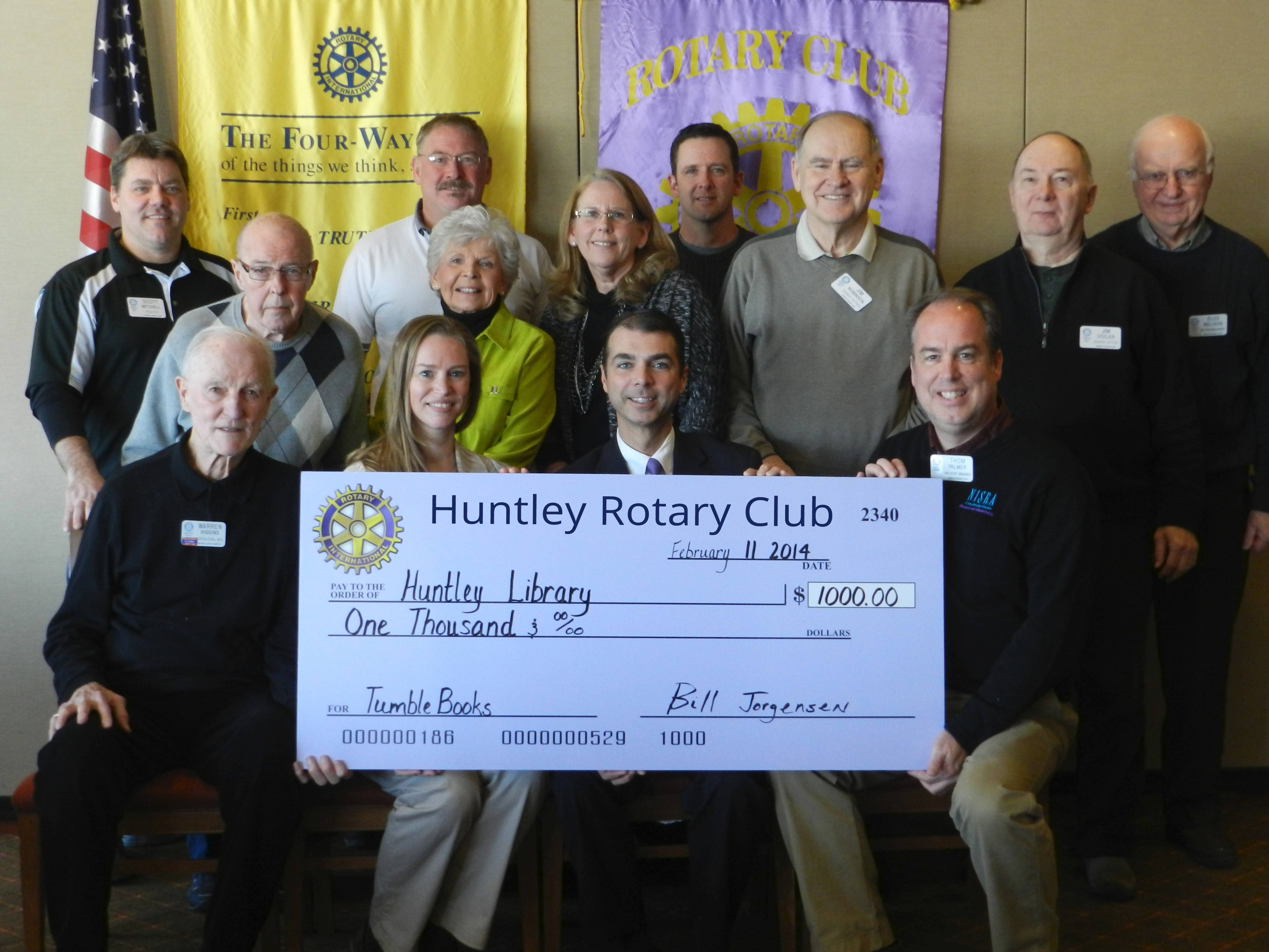 Huntley Rotary Club members with a check for TumbleBooks are, first row, from left, Warren Higgins, Leigh Ann Porsch, Bill Jorgensen, Thom Palmer; and standing, Scott Mitchell, Earl Ferris, Jim Drendel, Muriel Wright, Nancy Topalovich, Chad Alexander, Jim Robinson, Jim Uszler and Rudi Welvers.