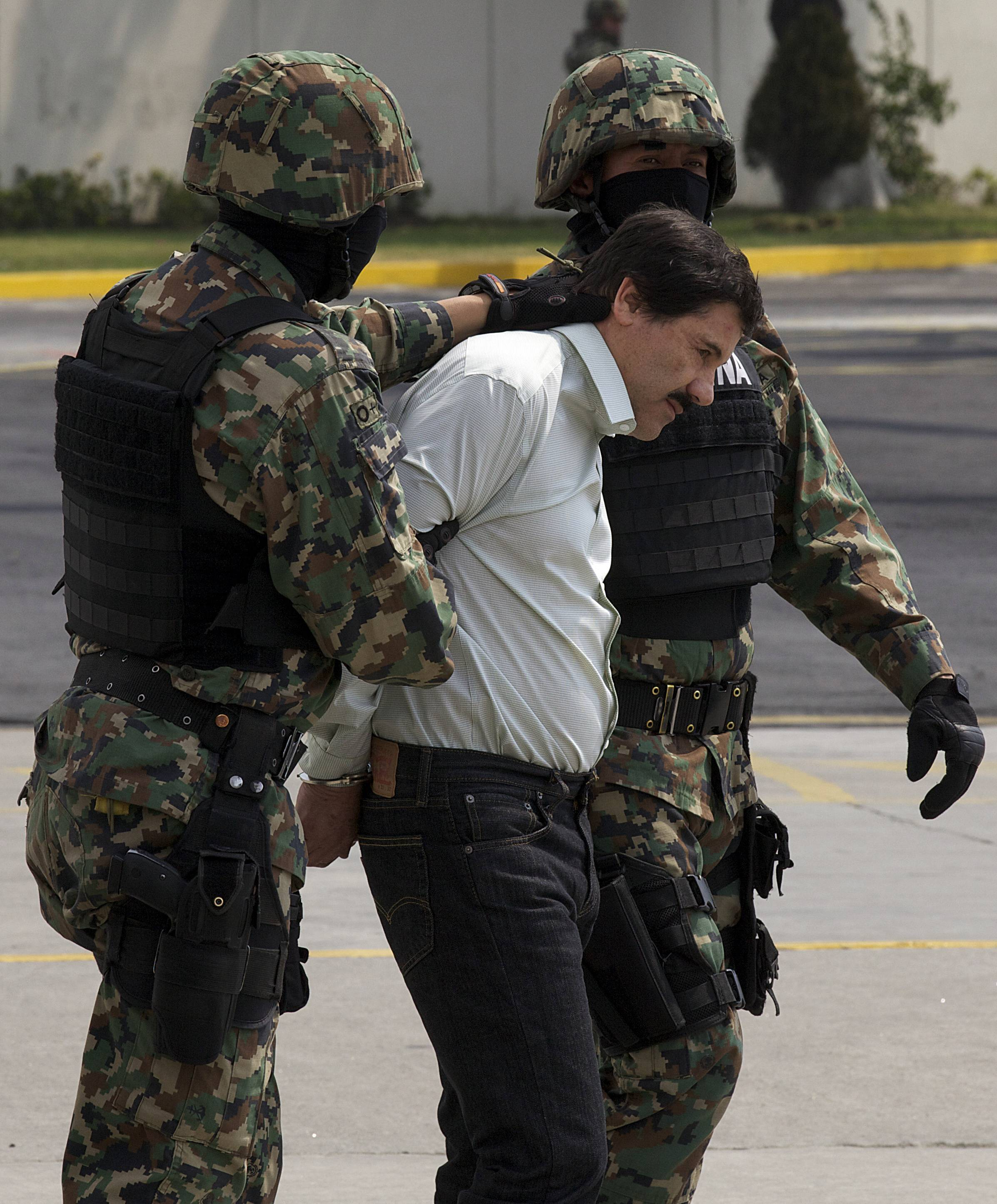 "Joaquin ""El Chapo"" Guzman is escorted to a helicopter in handcuffs Saturday by Mexican marines in Mexico City, Mexico."