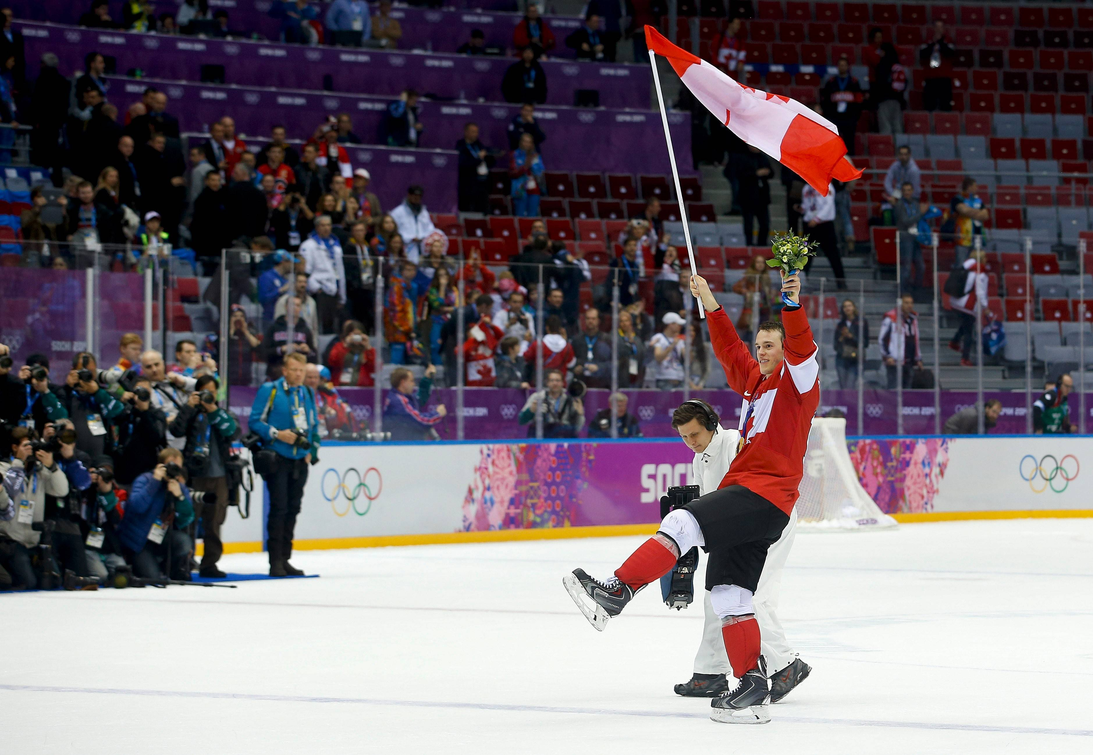 Canada forward Jonathan Toews skates around the rink waving the Canadian flag after Canada beat Sweden 3-0 in the men's gold medal ice hockey game Sunday at the 2014 Winter Olympics in Sochi, Russia. Toews will be back playing with the Blackhawks this week.
