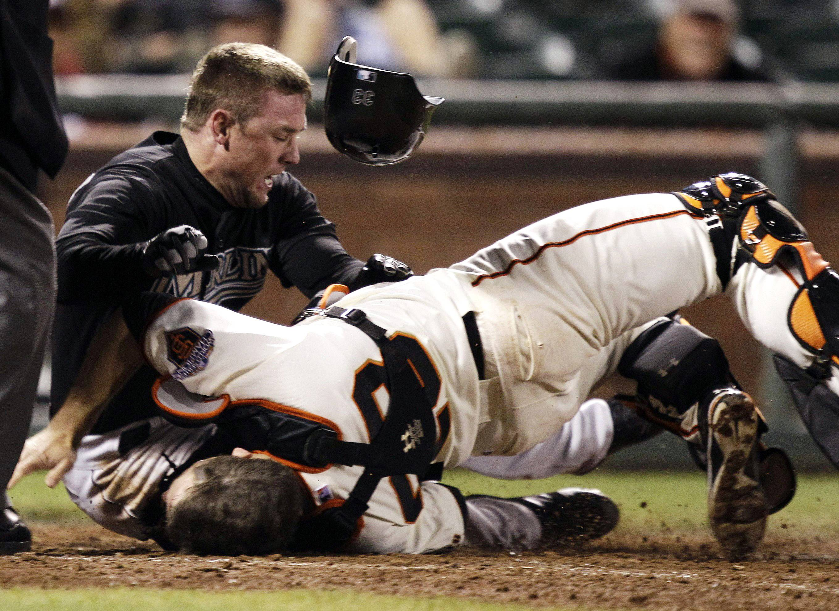 In this May 25, 2011 file photo, Florida Marlins' Scott Cousins, top, collides with San Francisco Giants catcher Buster Posey on a fly ball during the 12th inning of a baseball game in San Francisco. Cousins was safe for the go ahead run. A new rule, 7.13, was adopted by MLB and the players' association on a one-year experimental basis, the sides said Monday. The umpire crew chief can use the new video-review system to determine whether the rule was violated.