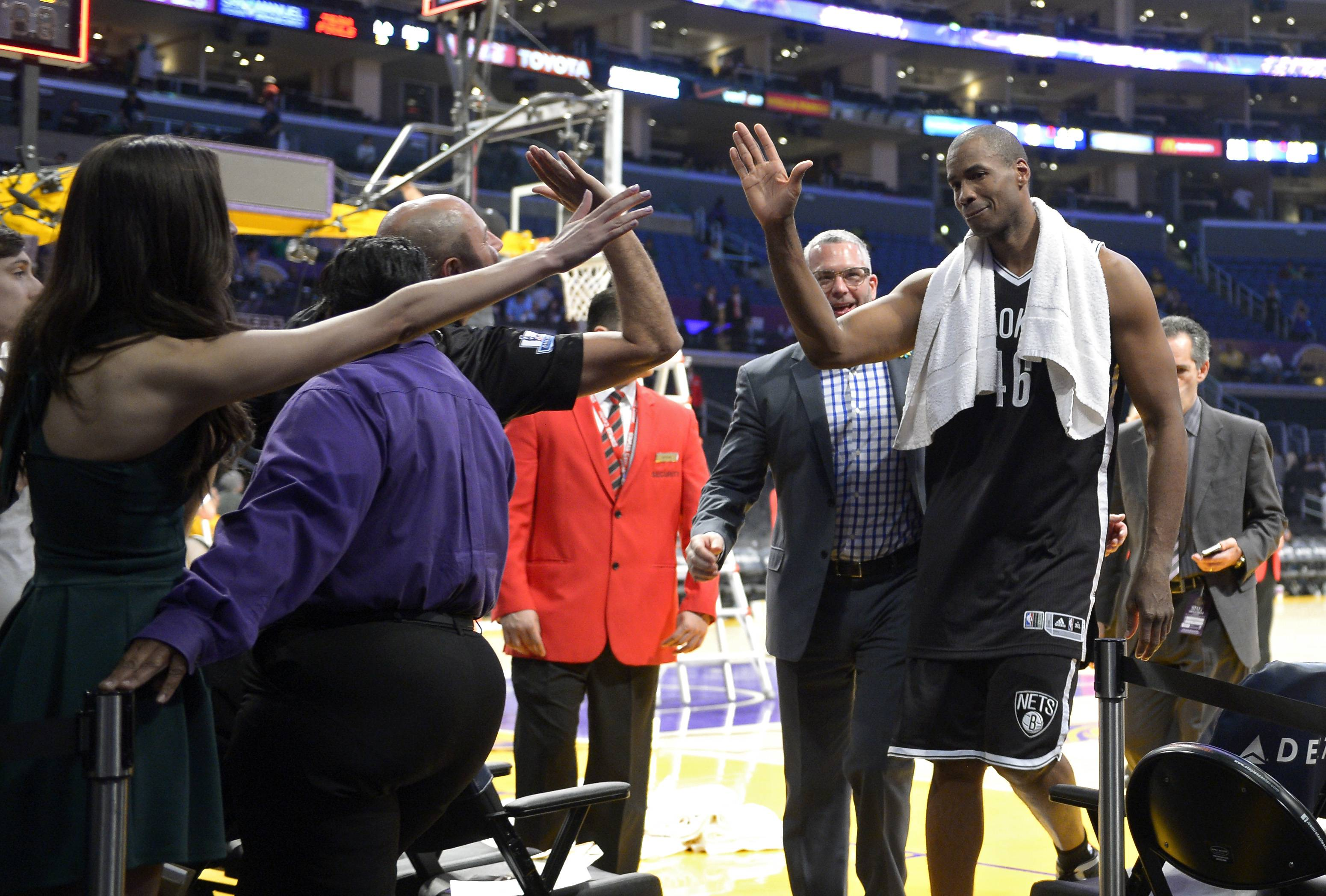 Brooklyn Nets center Jason Collins, right, is congratulated by fans after they defeated the Los Angeles Lakers in an NBA basketball game Sunday in Los Angeles. Brooklyn won 108-102.