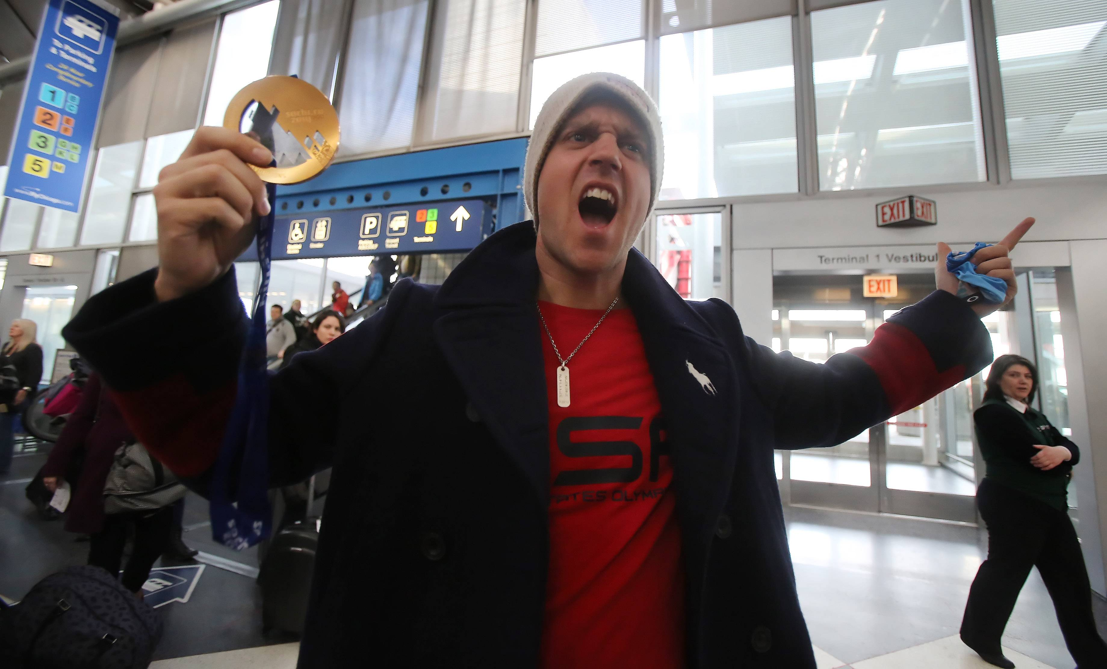 Snowboarder Alex Deibold shows off his bronze medal as about 20 members of Team USA stopped at O'Hare International Airport Monday afternoon on their way home from the 2014 Winter Olympics in Sochi, Russia.