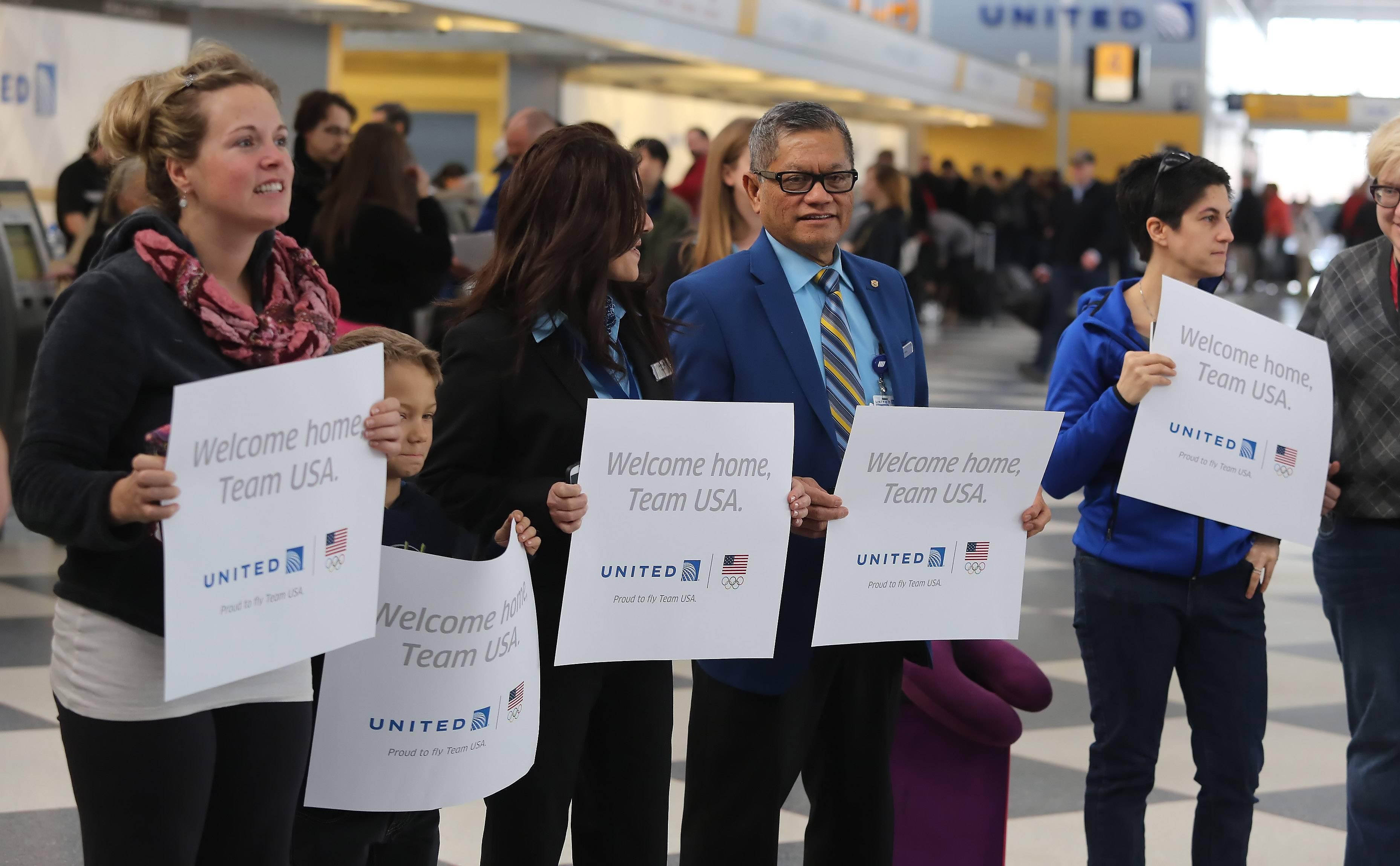 United employees and travelers held up signs welcoming home members of Team USA, after about 20 skiers, snowboarders and curlers came through O'Hare International Airport Monday, on their way home from the Winter Olympics in Sochi, Russia. United Airlines is the official airline of Team USA.