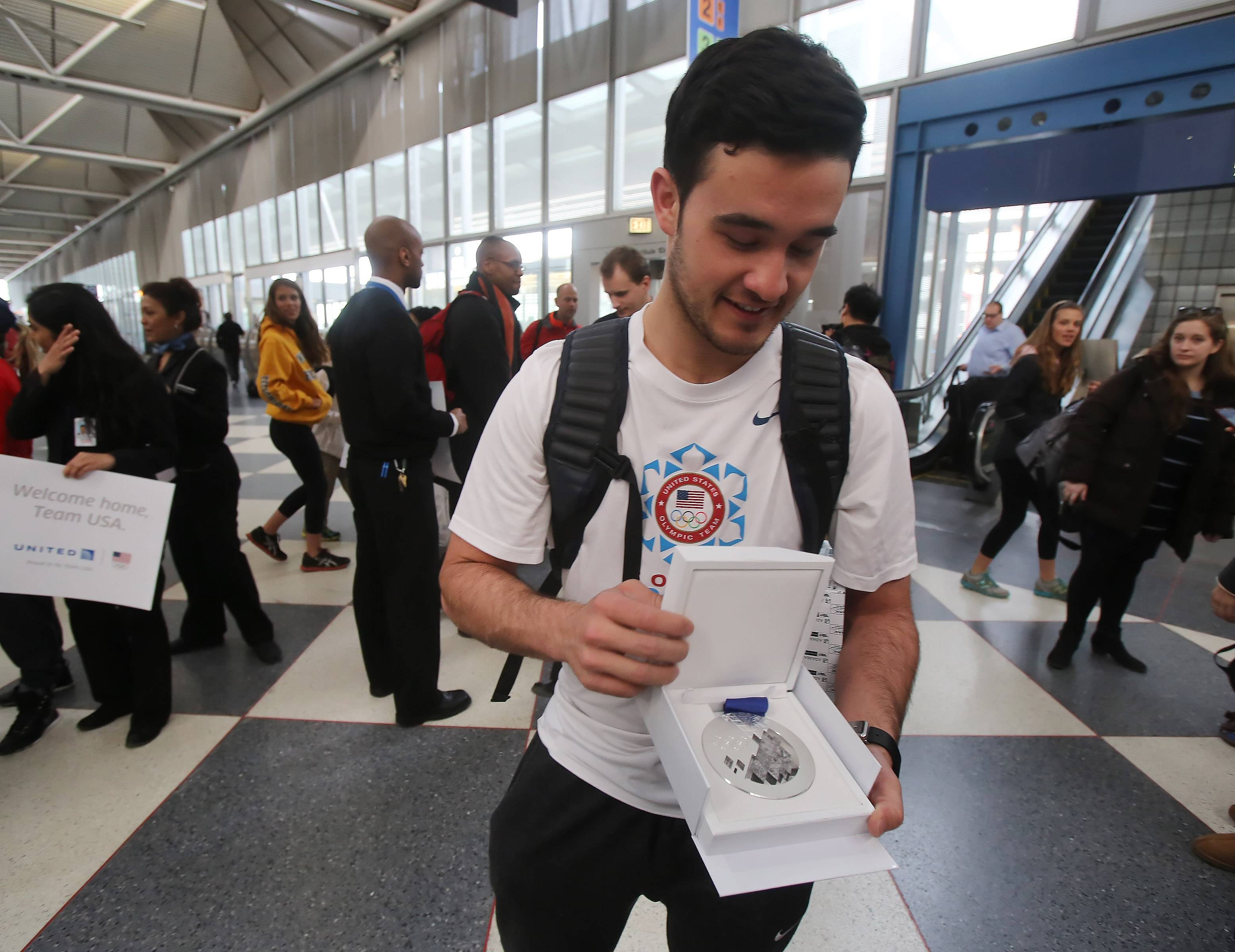 Speed skater Eddy Alvarez shows the silver medal he won at the Winter Olympics in Sochi while passing through O'Hare International Airport Monday, on his way home to Salt Lake City, Utah.